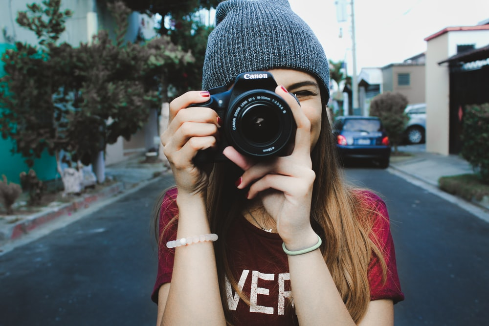 woman wearing red t-shirt and gray knitted cap standing on concrete road using Canon bridge camera during daytime