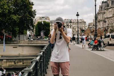 man holding DSLR camera beside bridge