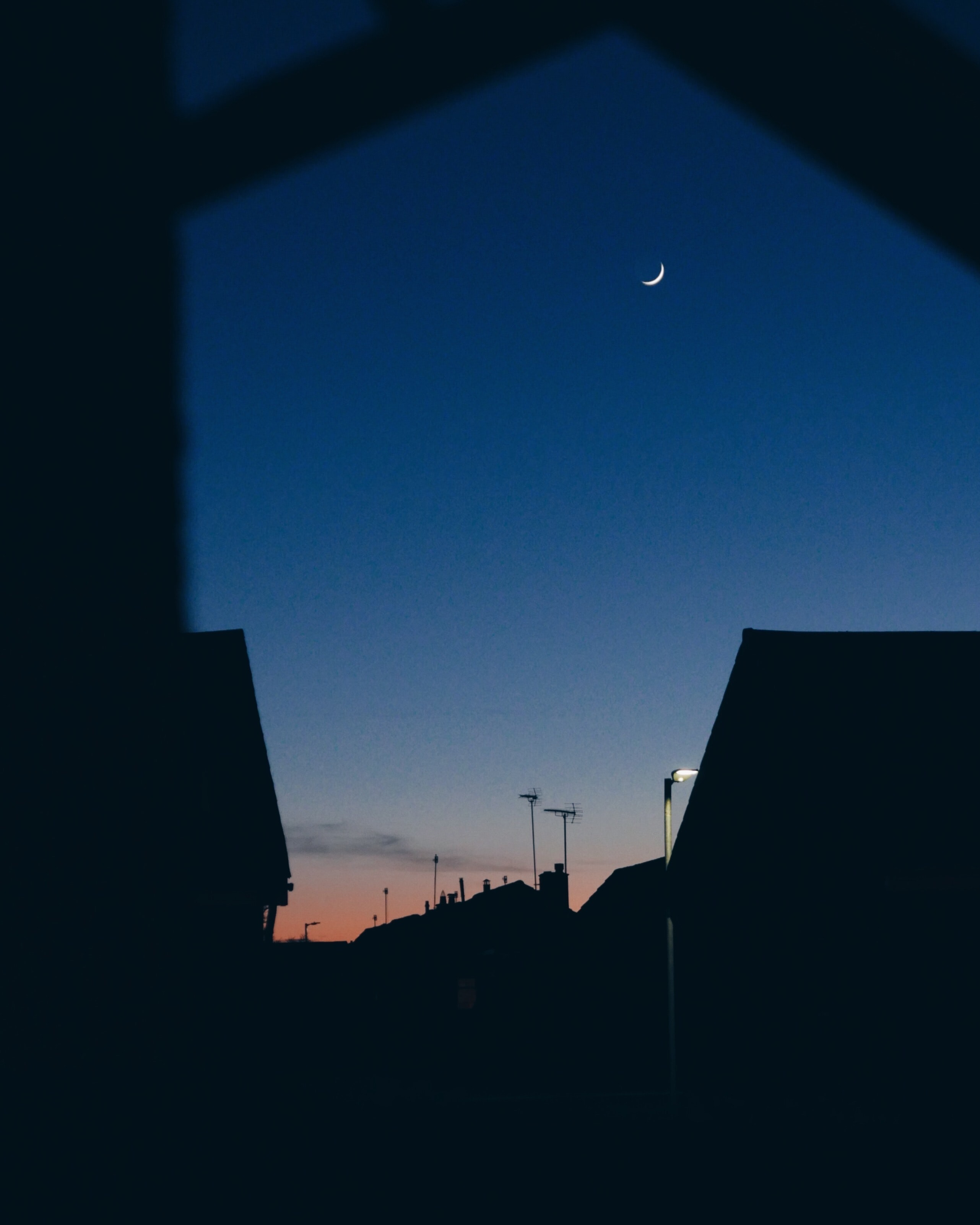 The crescent moon as seen through silhouetted houses in Troon at night.