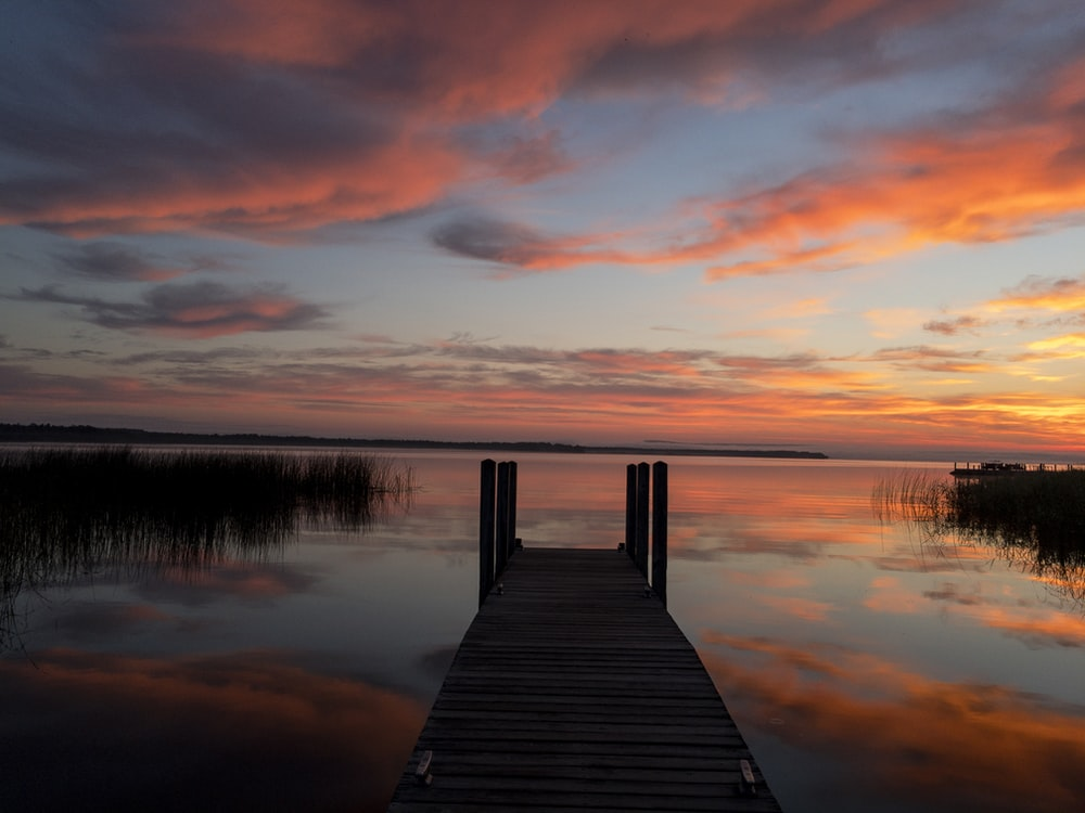 black wooden dock on body of water during golden hour