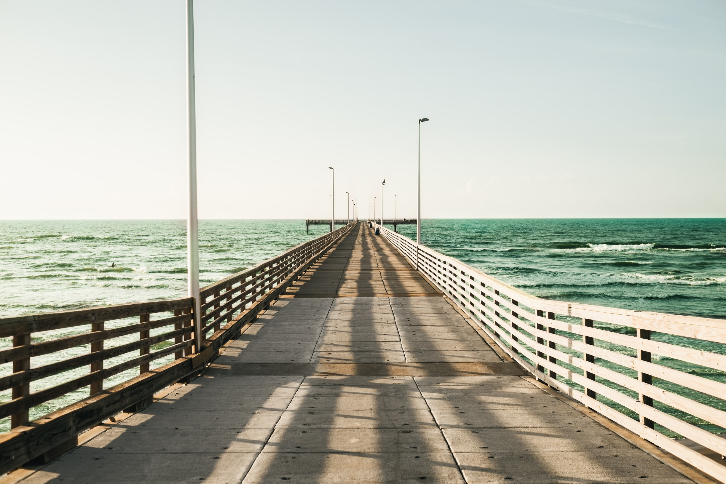 A wide wooden pier reaching out into the sea