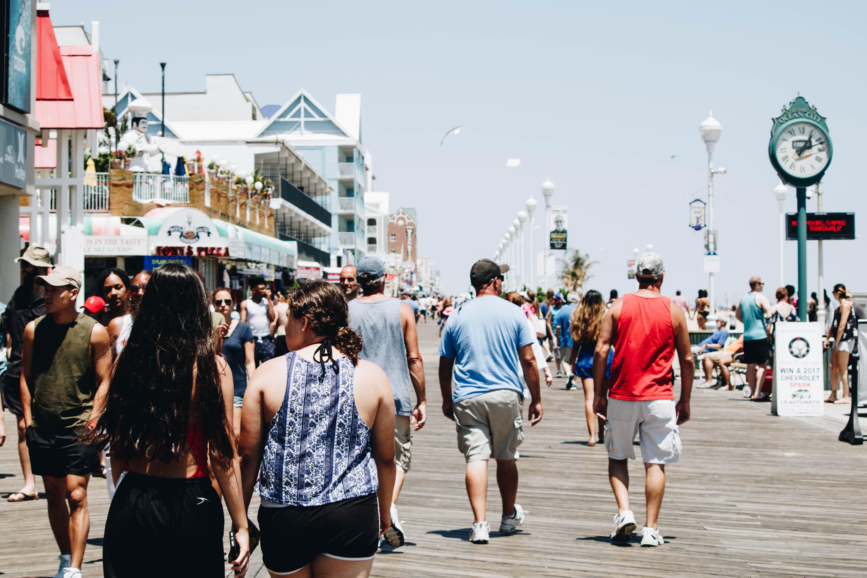 Diverse crowd of tourists walk along a pier in Ocean City