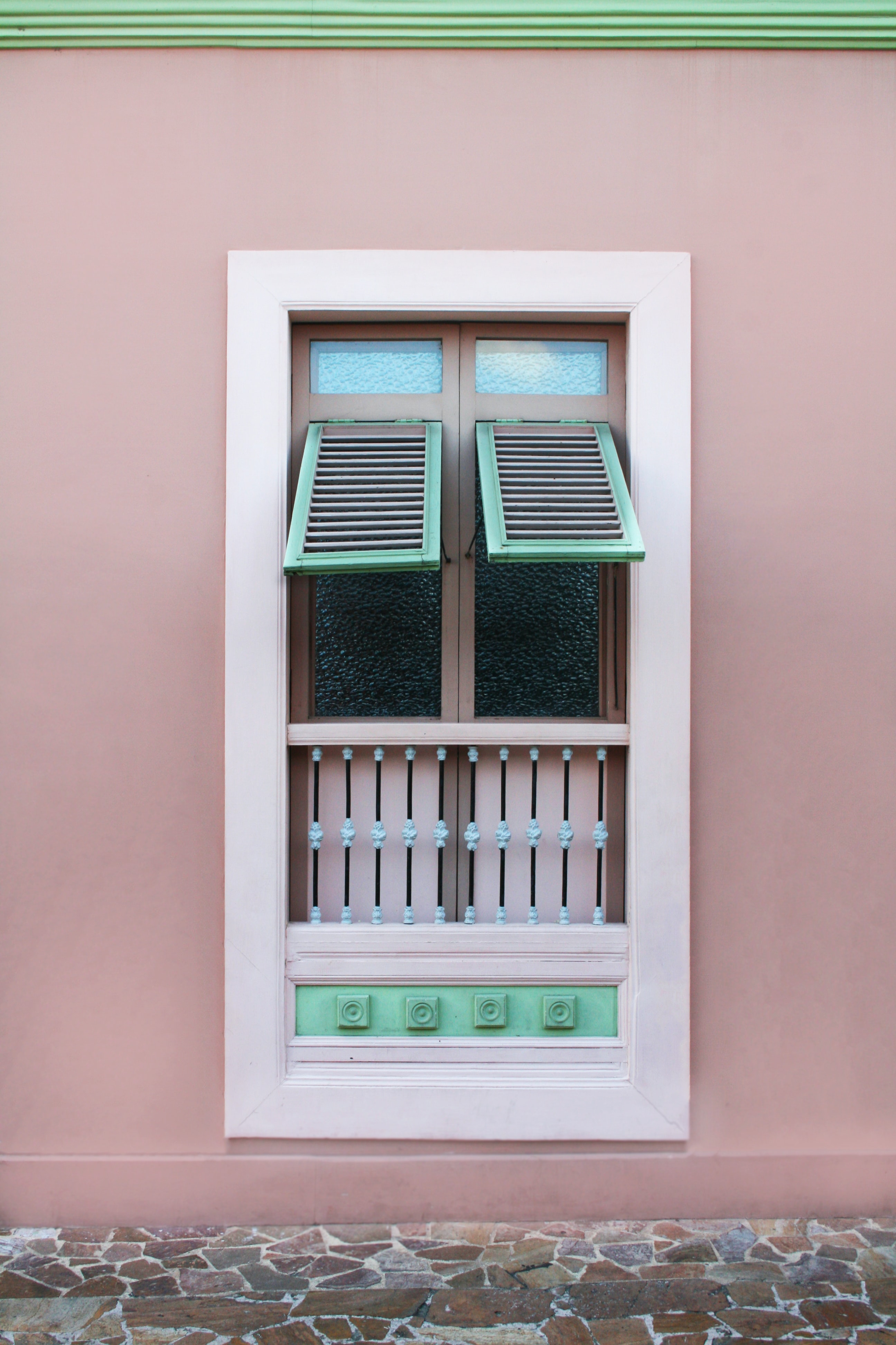 opened white teal and brown wooden louvered window panel