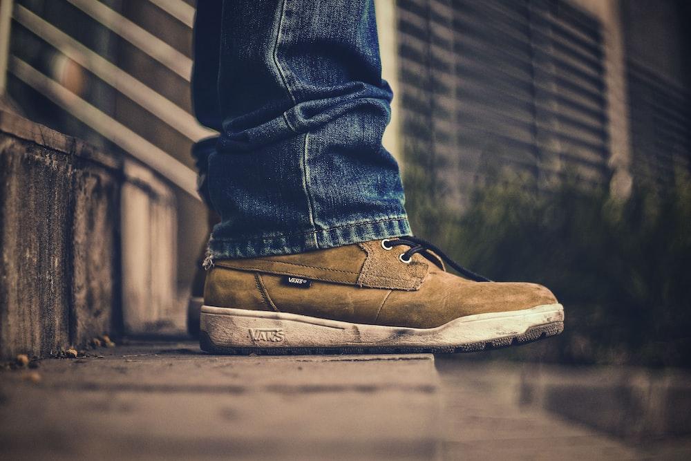 unpaired brown sneaker and blue denim pants