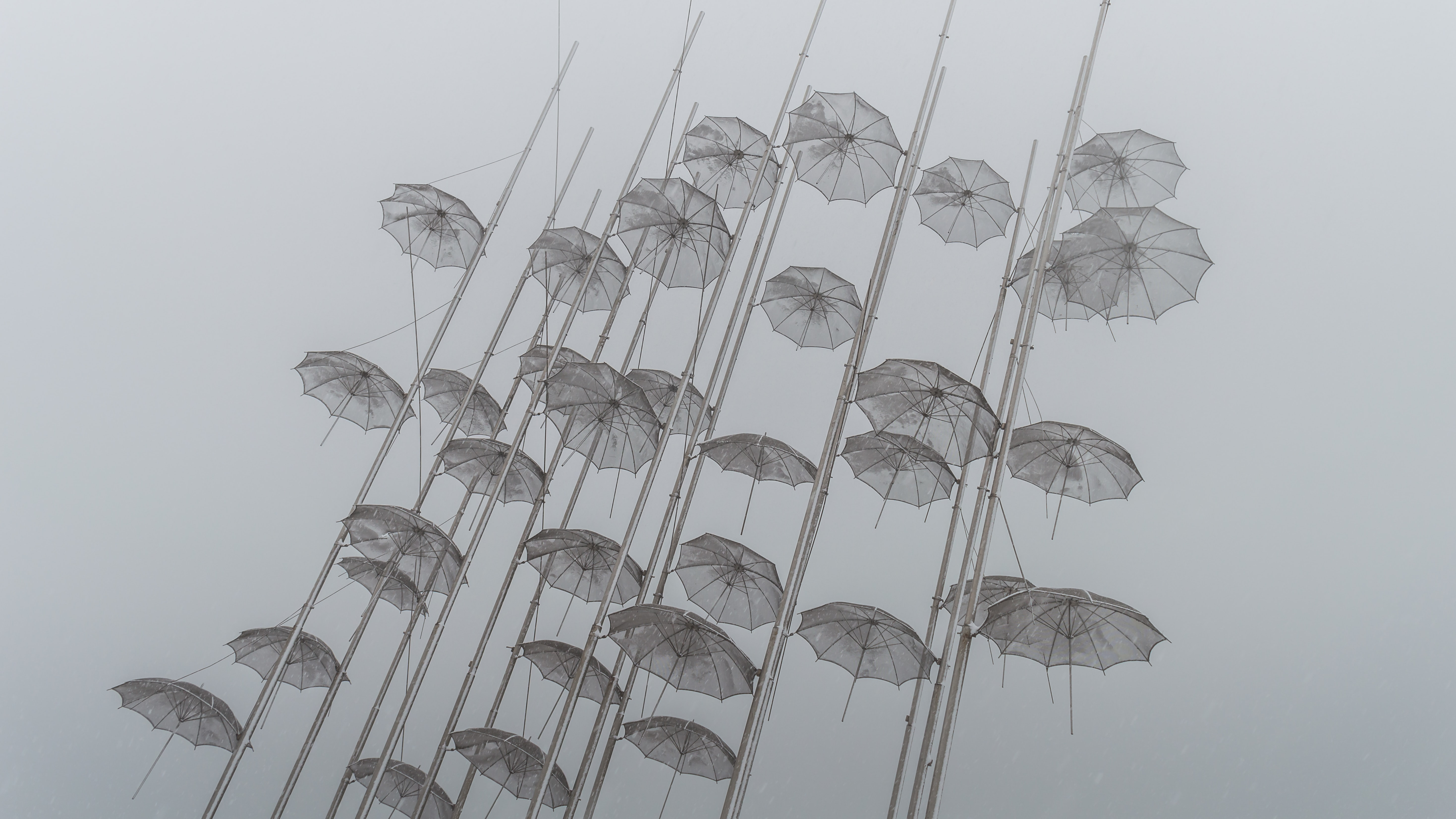 Dozen of transparent umbrellas on the flag poles at New Beach Thessaloniki