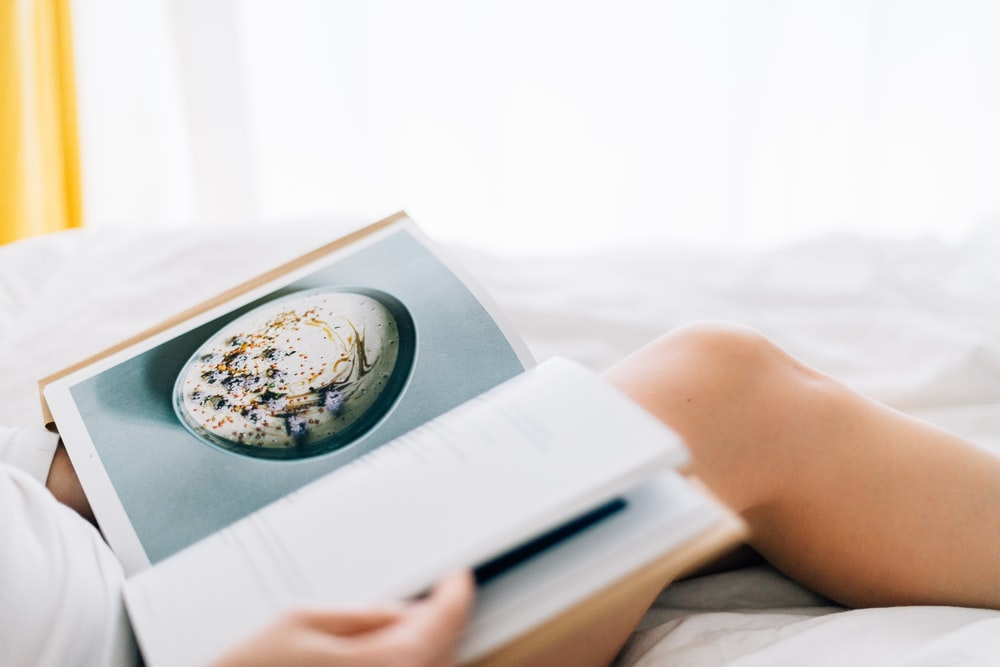 person holding open magazine while laying on bed