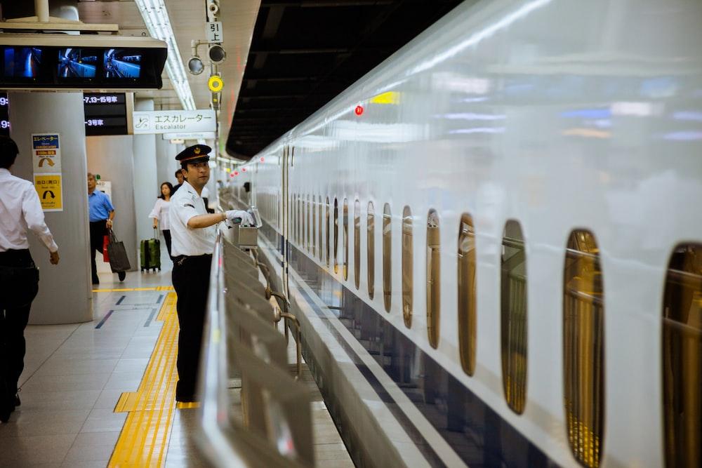 man standing behind railing of subway station platform