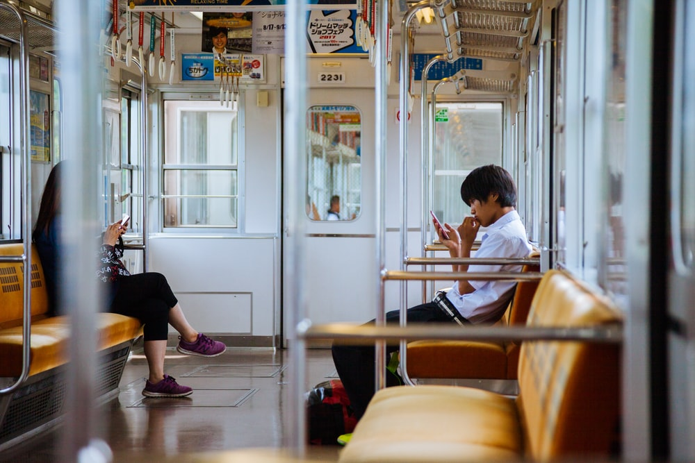 man and woman sitting chair inside the train