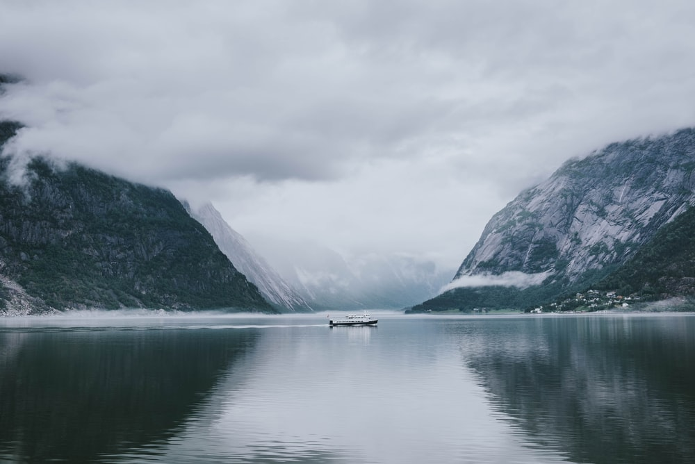 white and gray boat in the middle of calm body of water near mountain under white sky