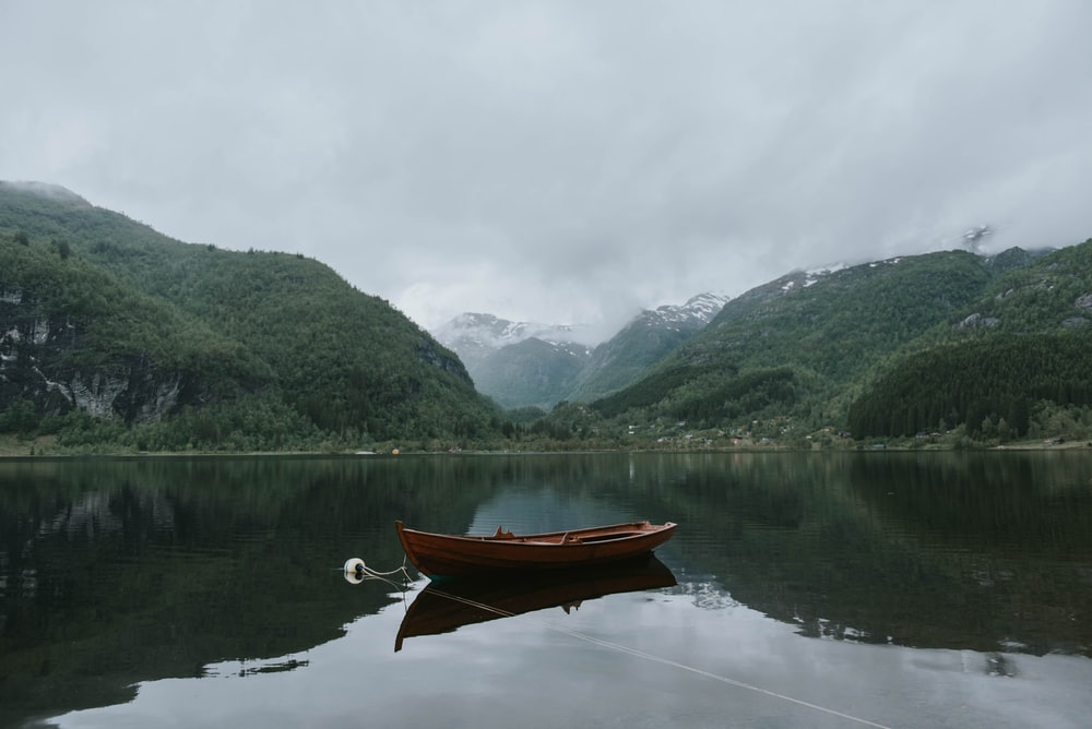 brown boat on body of water near green mountains under white sky at daytime
