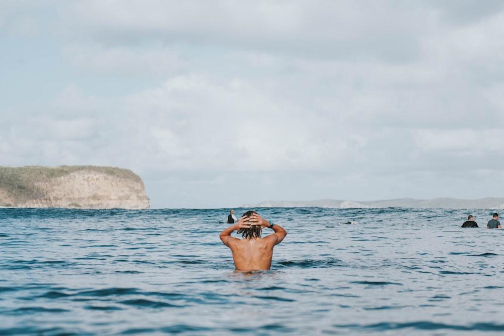 man swimming near ocean during daytime