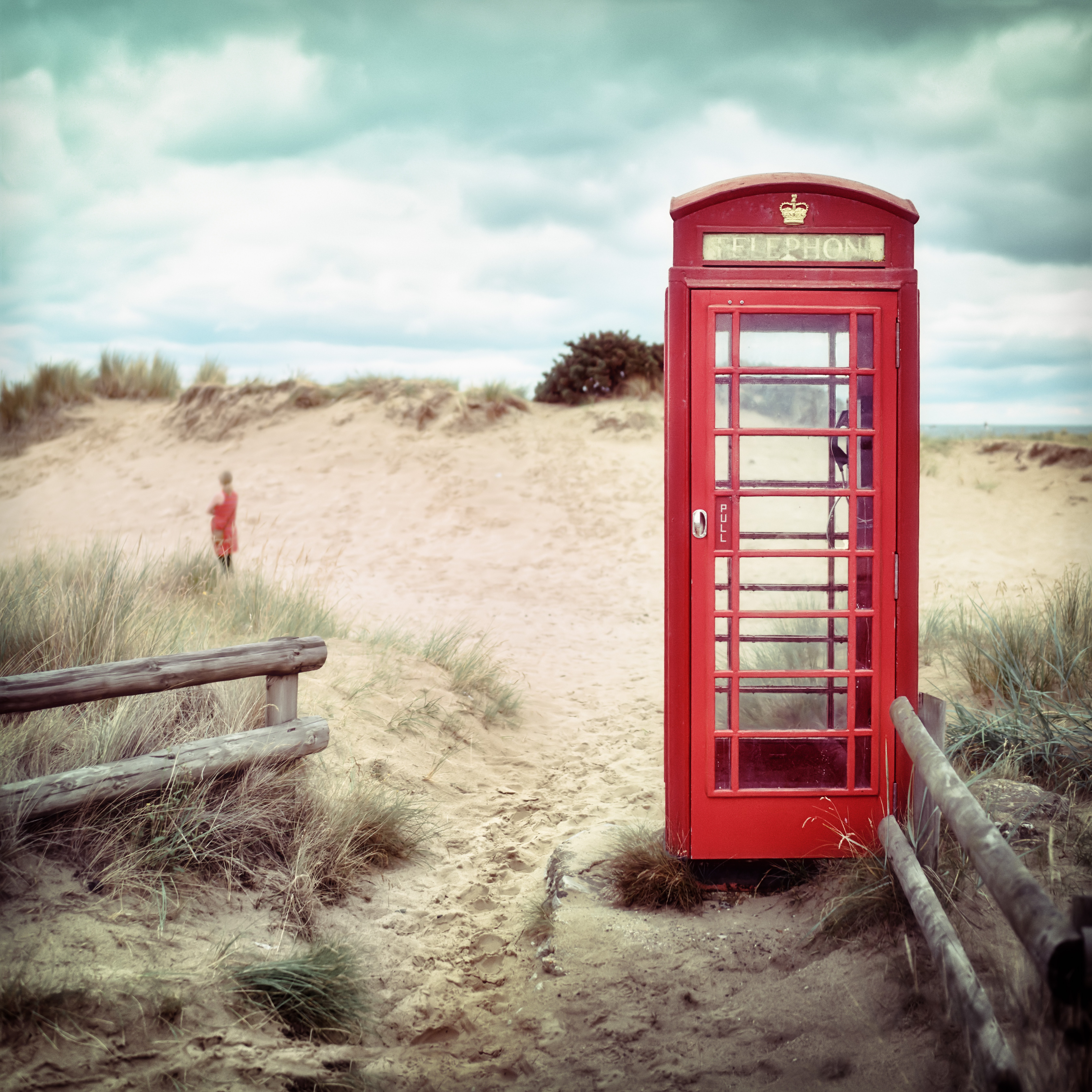A red telephone booth sitting on a beach.