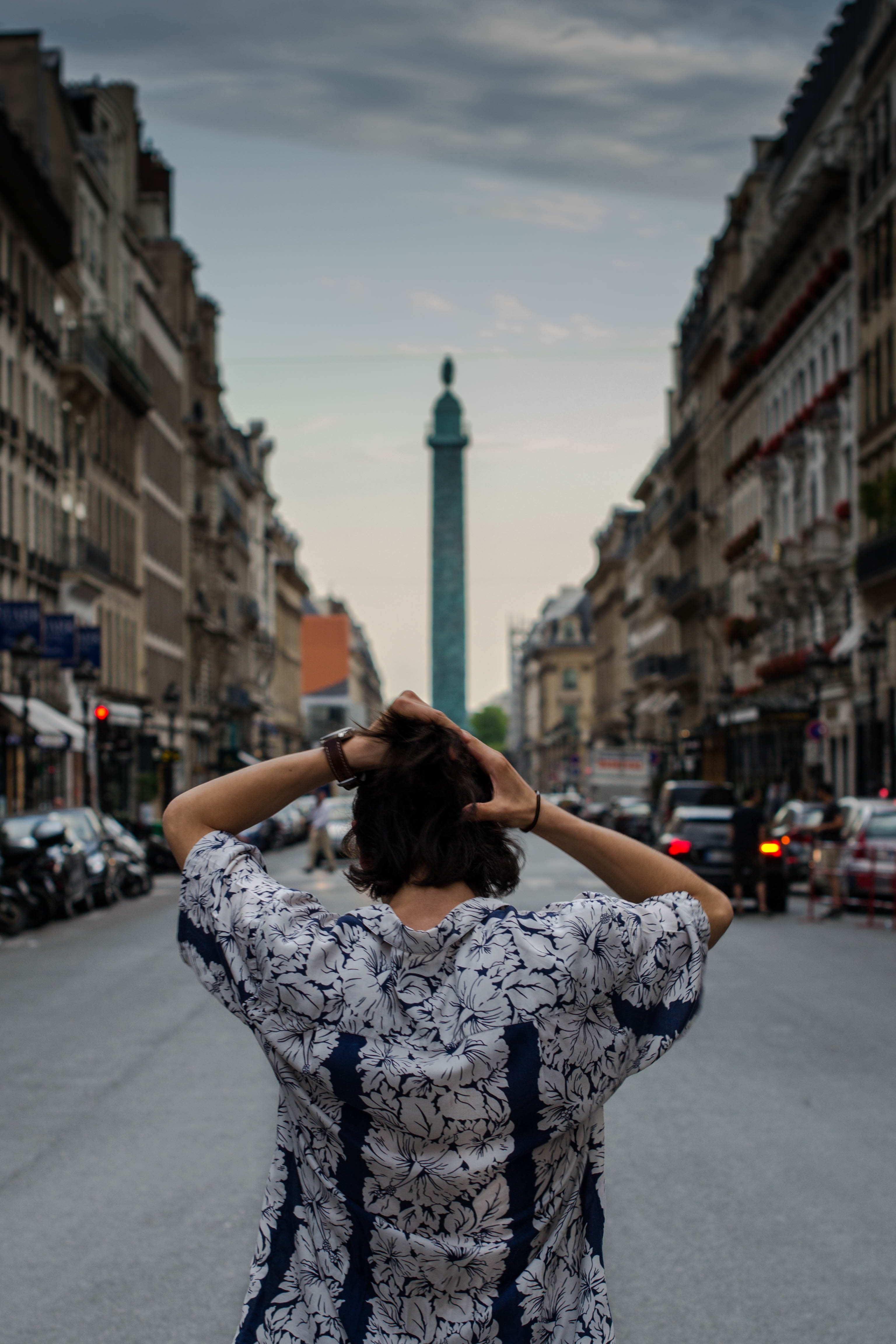 A person facing away from the camera looks down a street toward a monument in Paris