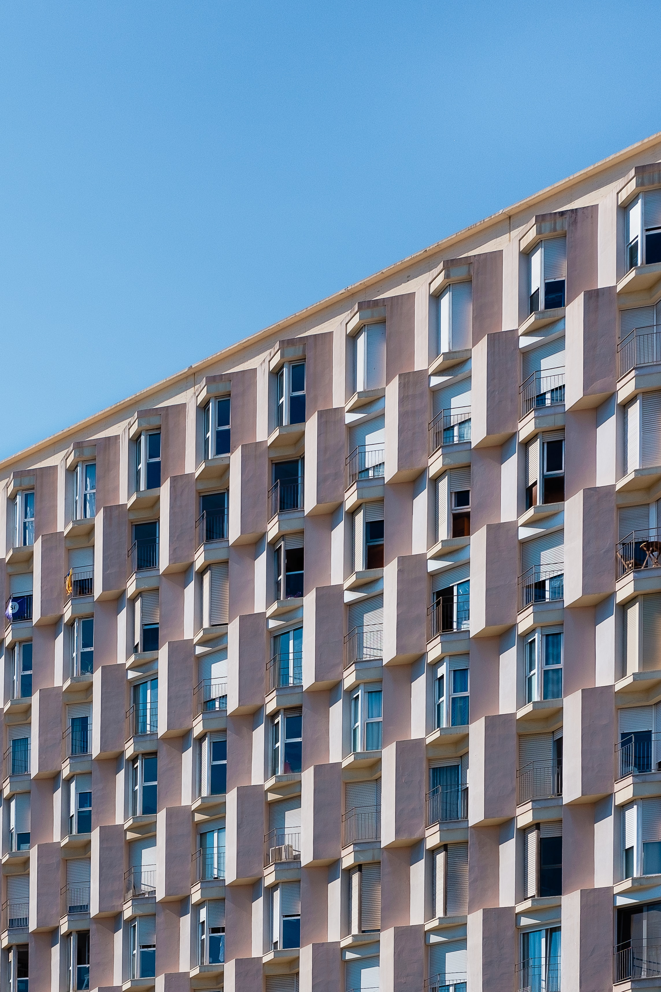 A pink residential building facade in Barcelona under a blue sky