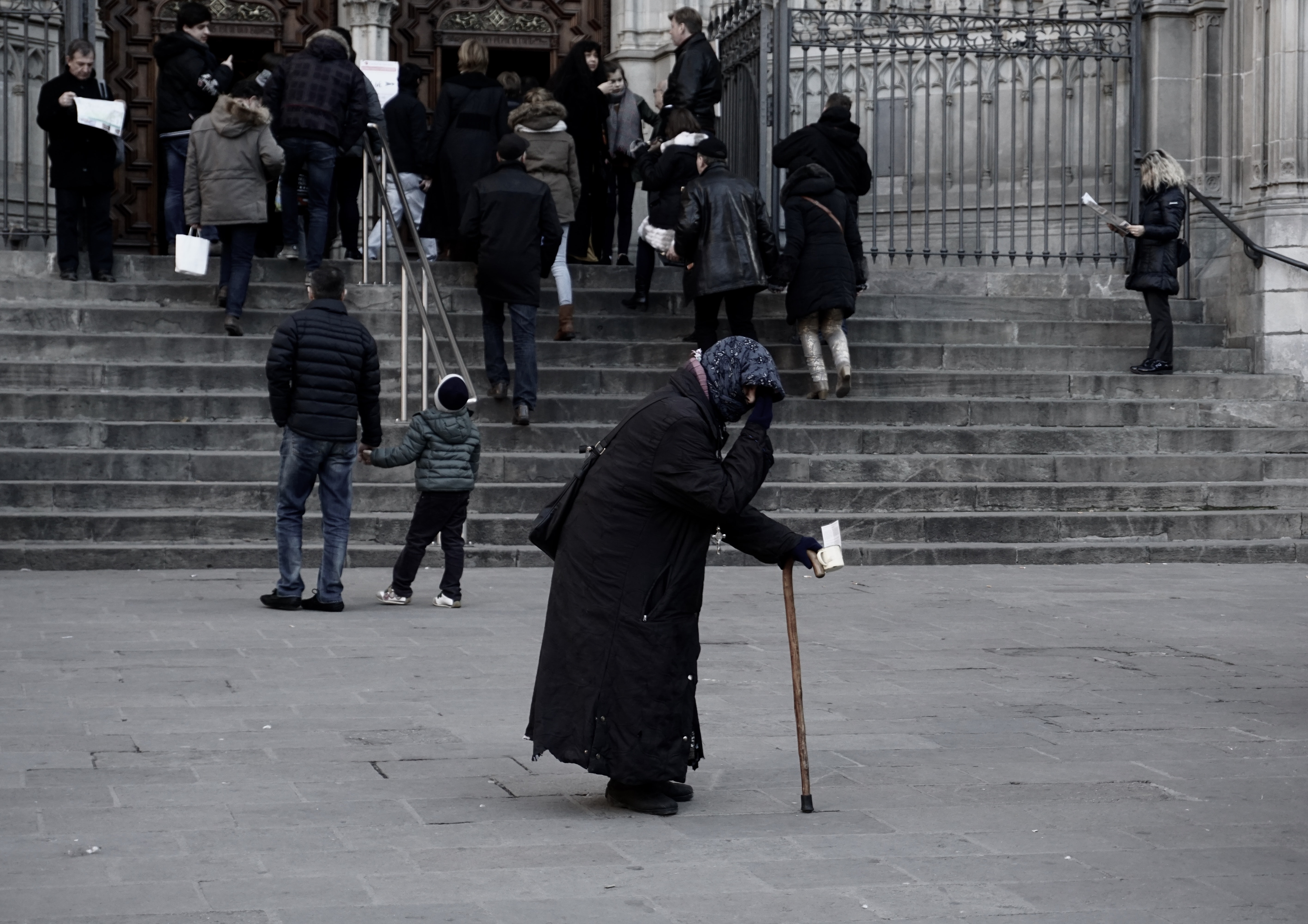Elderly person with a walking cane standing near a crowd of people