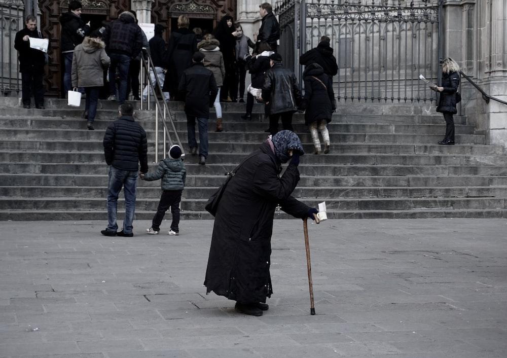 woman in black dress holding brown walking cane