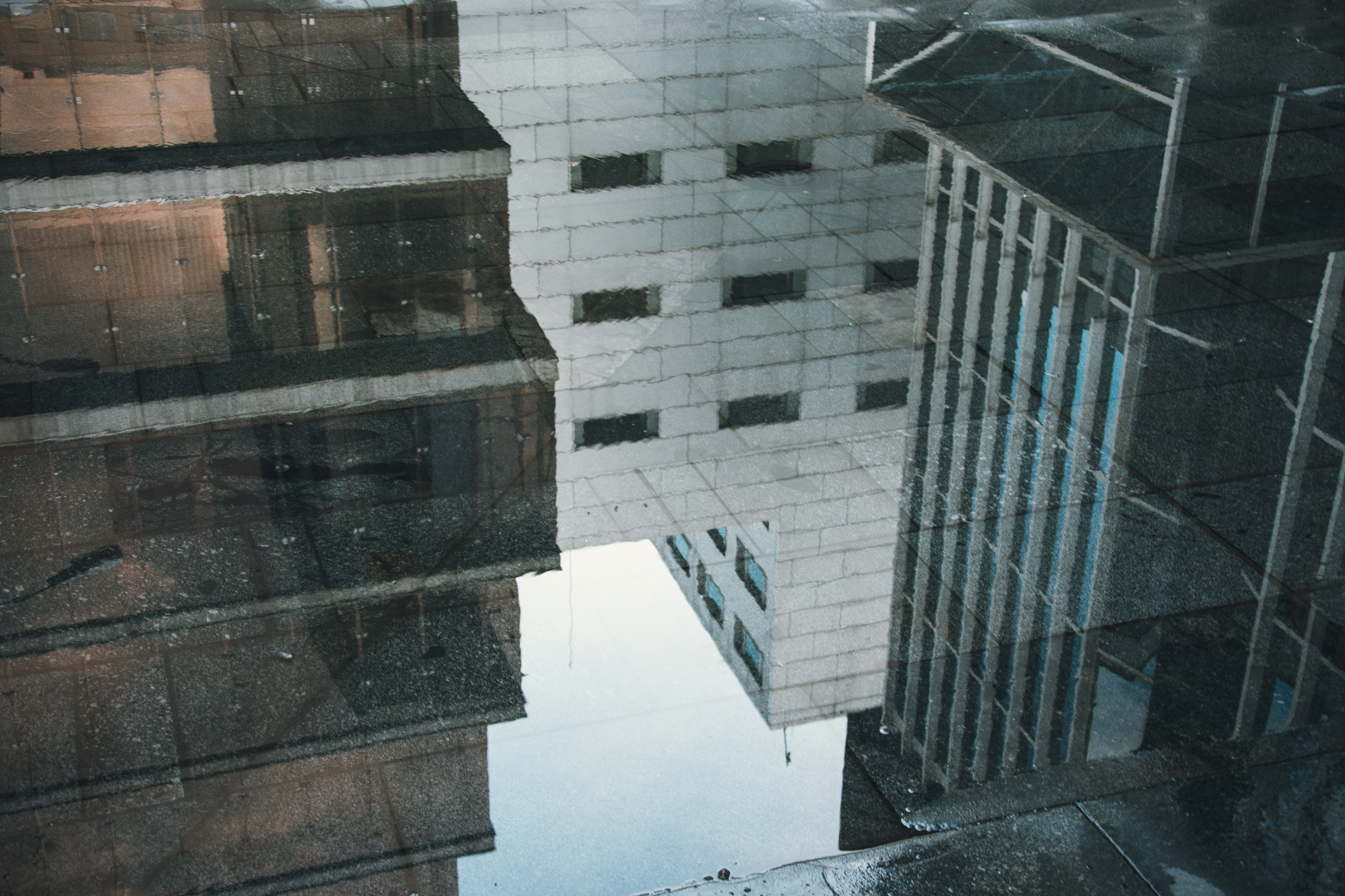 Buildings reflected in a puddle on a sidewalk
