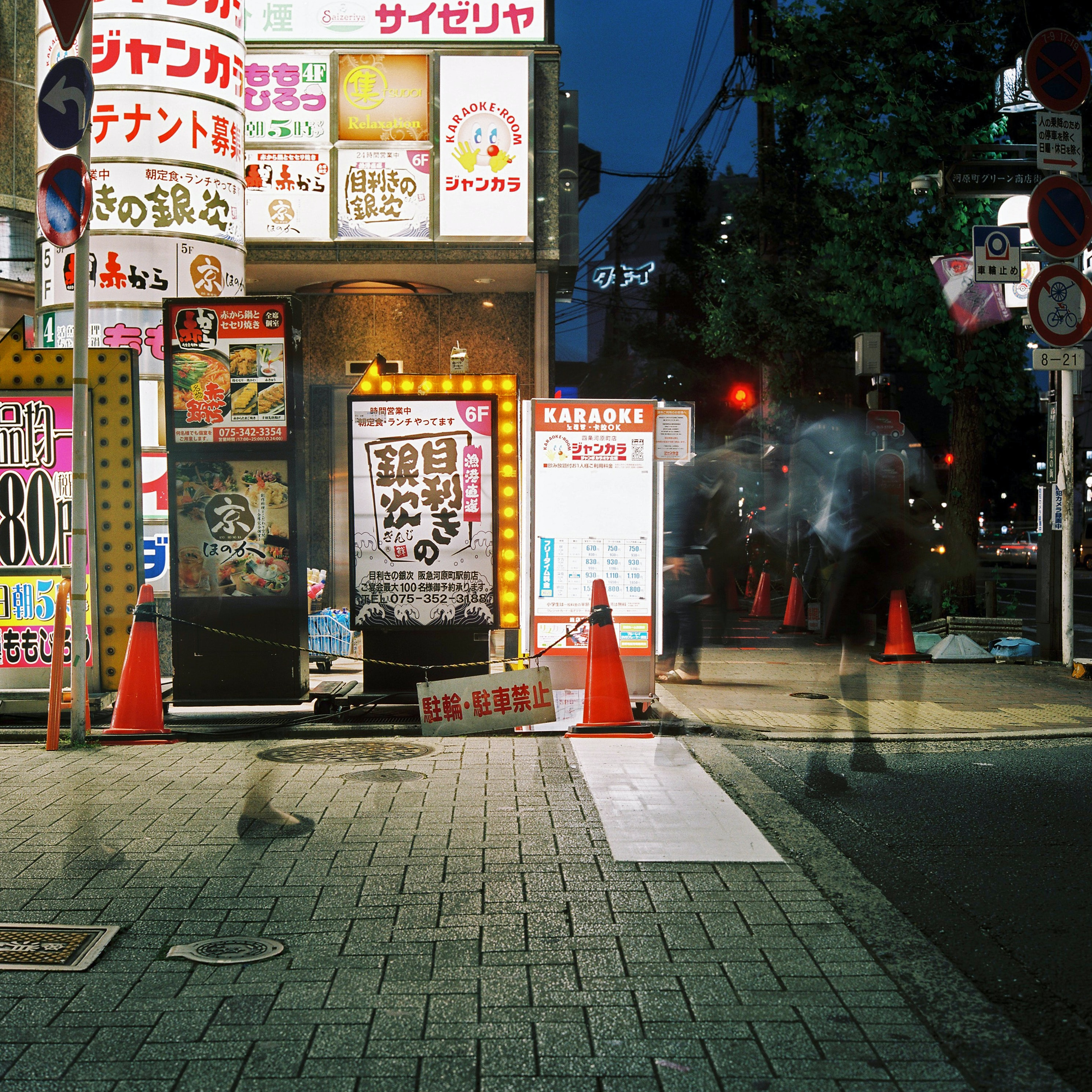 A long-exposure shot of bright advertisements on a building wall in Kyoto at night