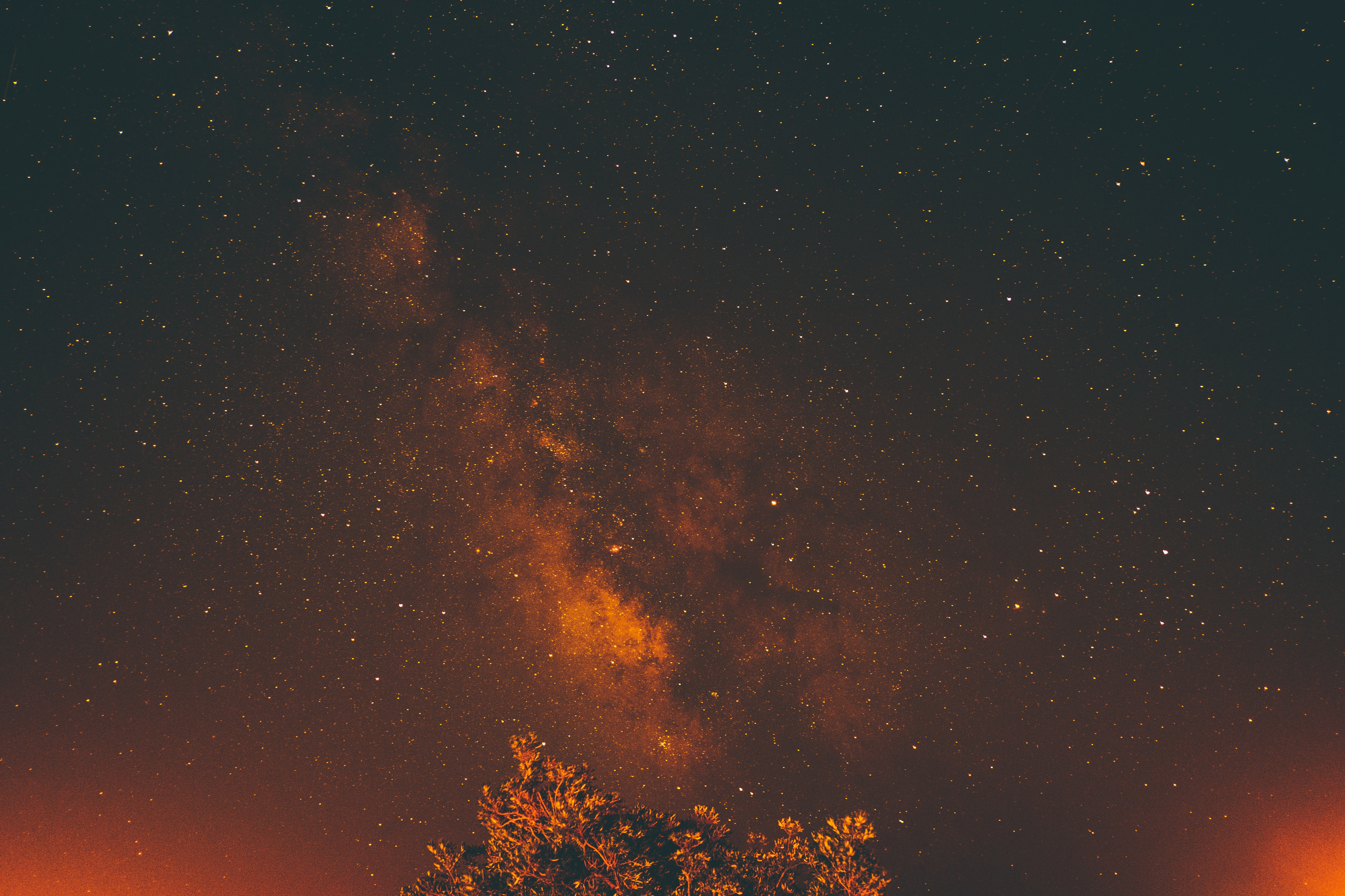The milky way and night sky with an orange hue