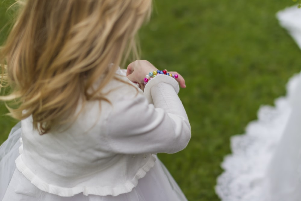 girl wearing white dress holding her bracelet