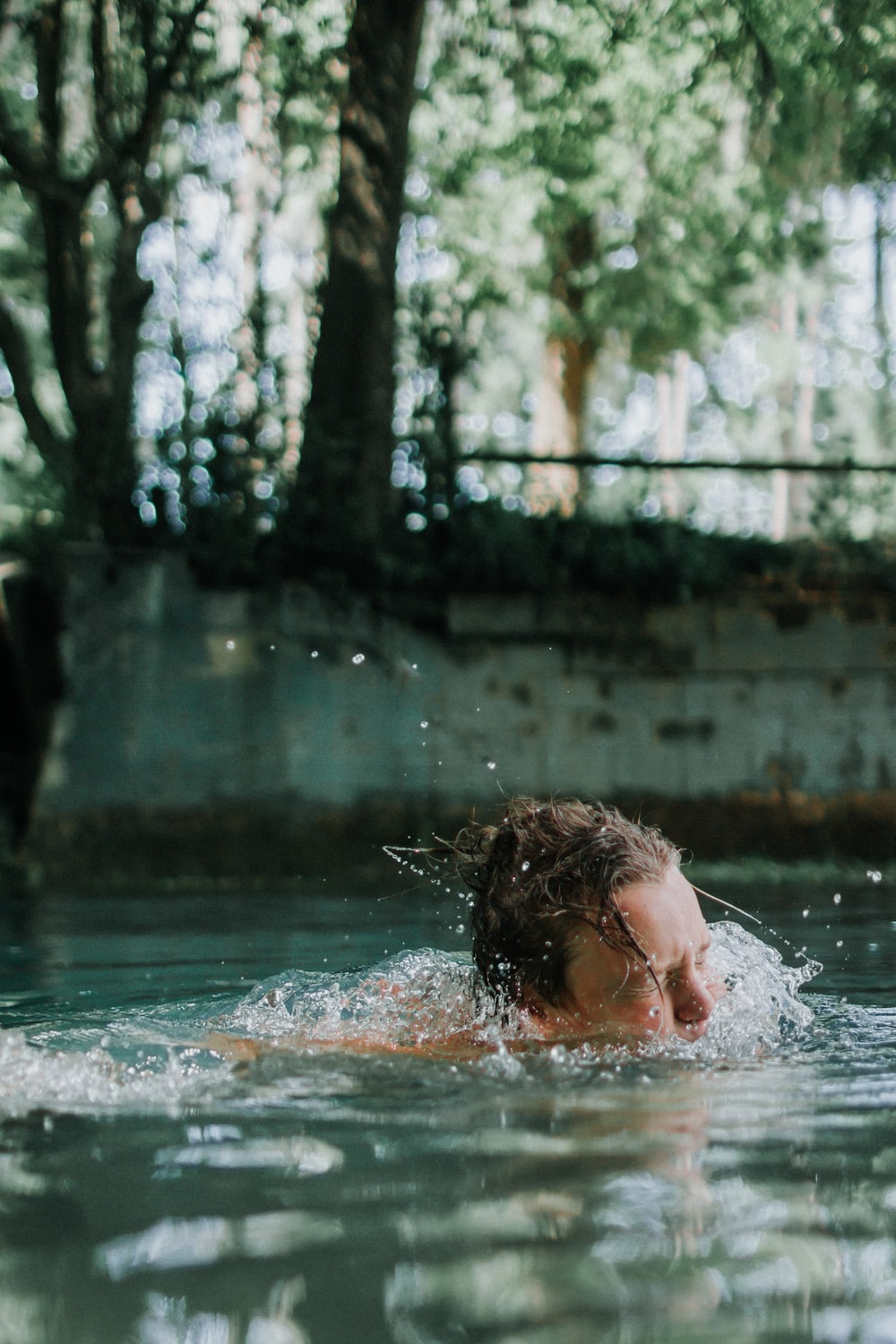 woman swimming on body of water during daytime