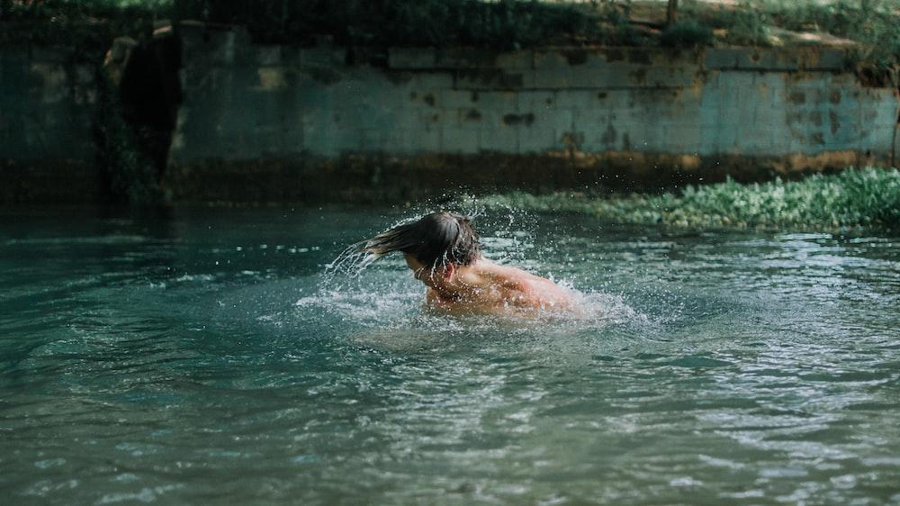 man swimming on water during daytime