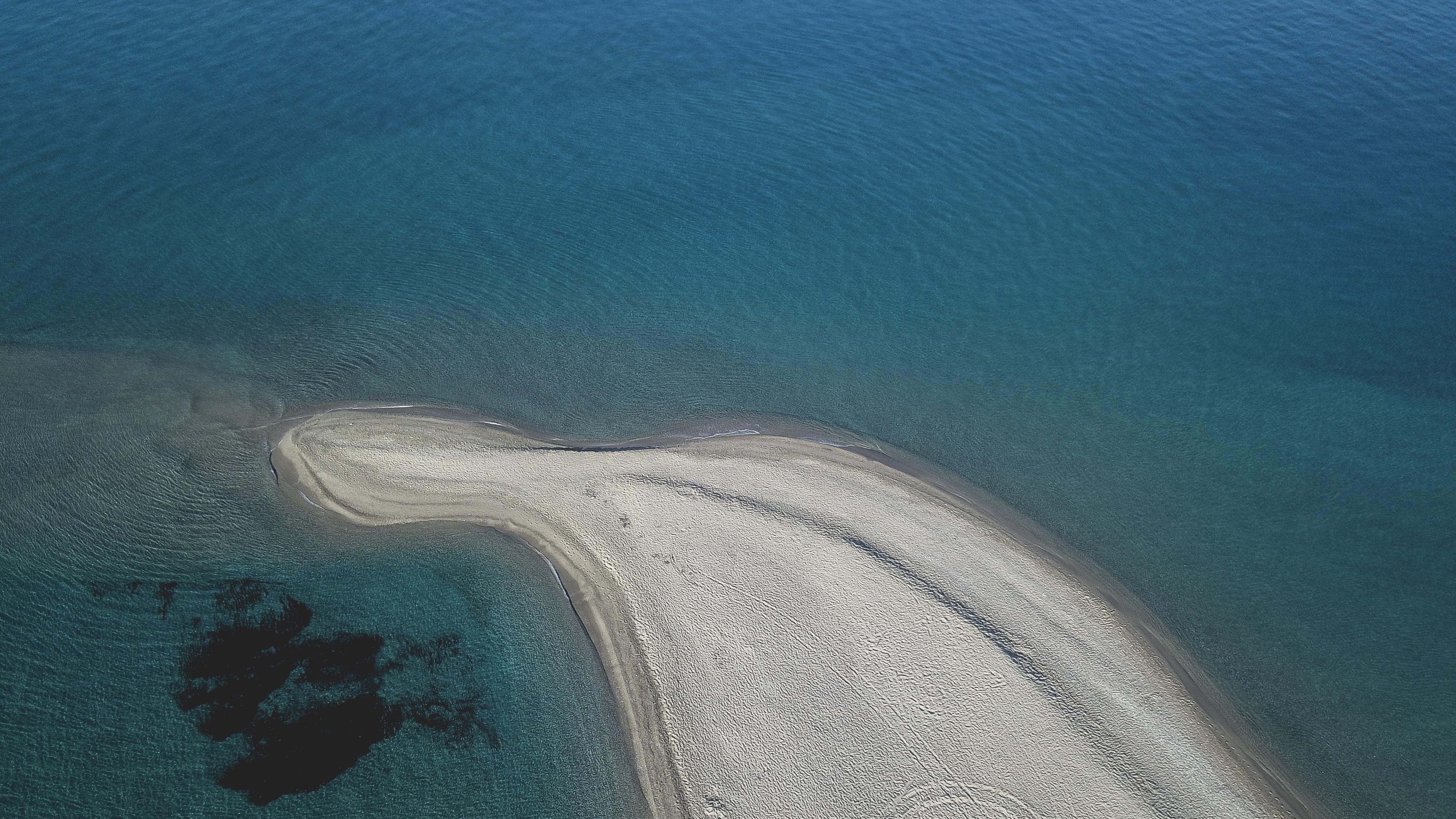 Drone shot of sand in clear blue ocean, Μύτη Ποσειδίου