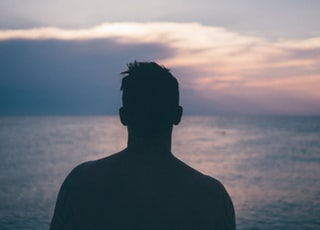 silhouette photography of man standing near sea