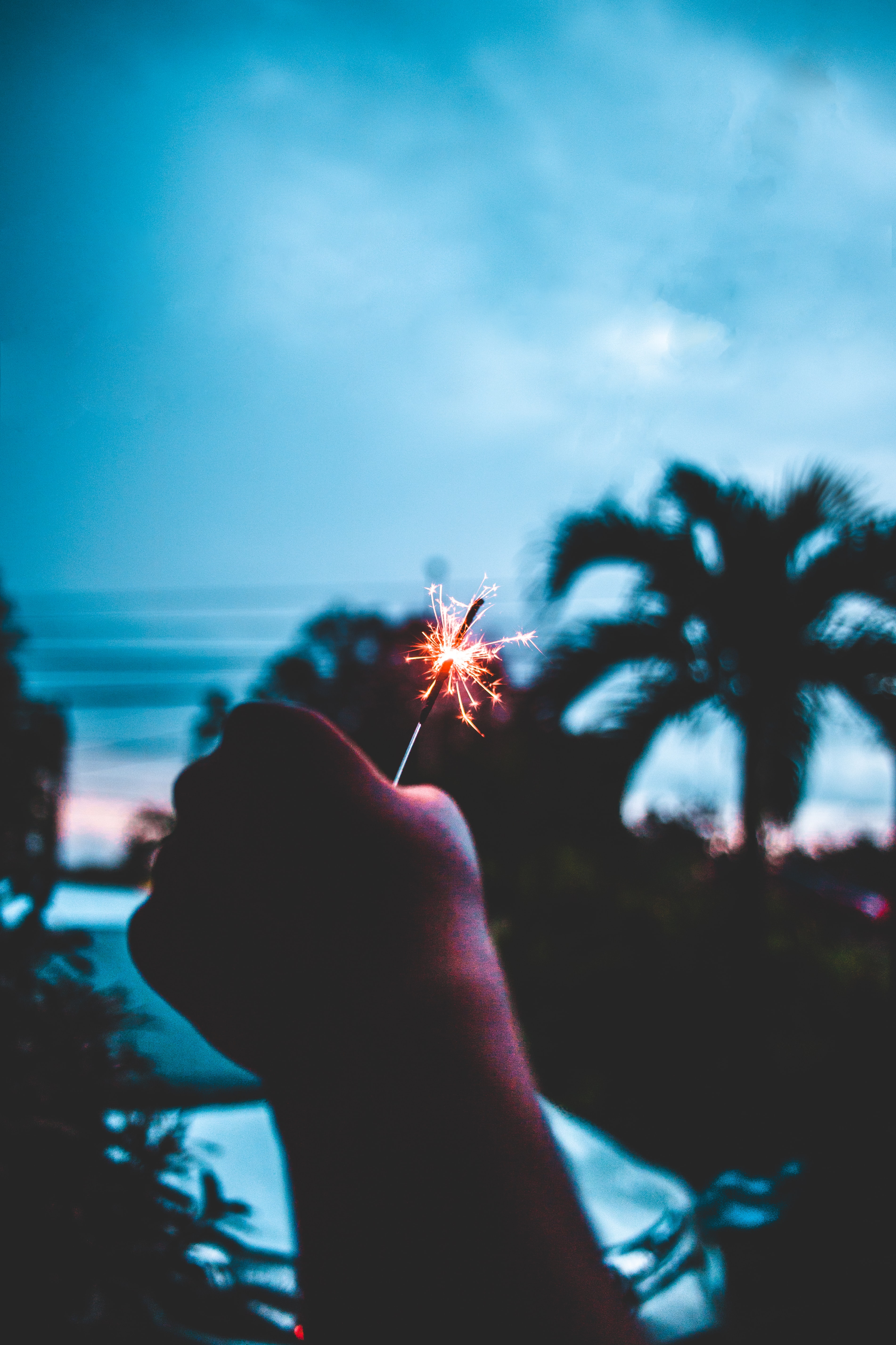 A person holding a lit sparkler in the air.