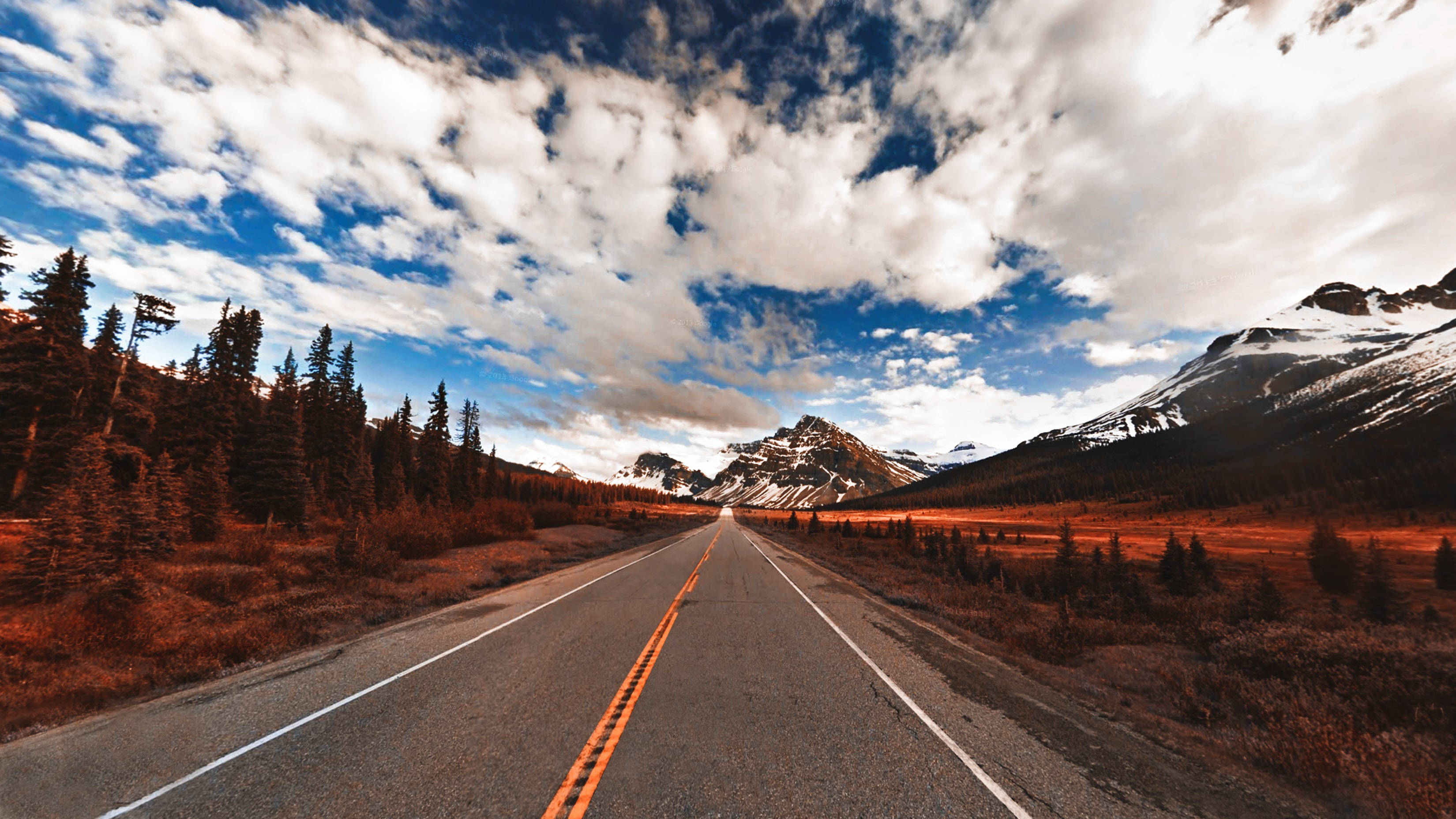 A road in Alberta surrounded by snowcapped mountains, blue sky, and clouds