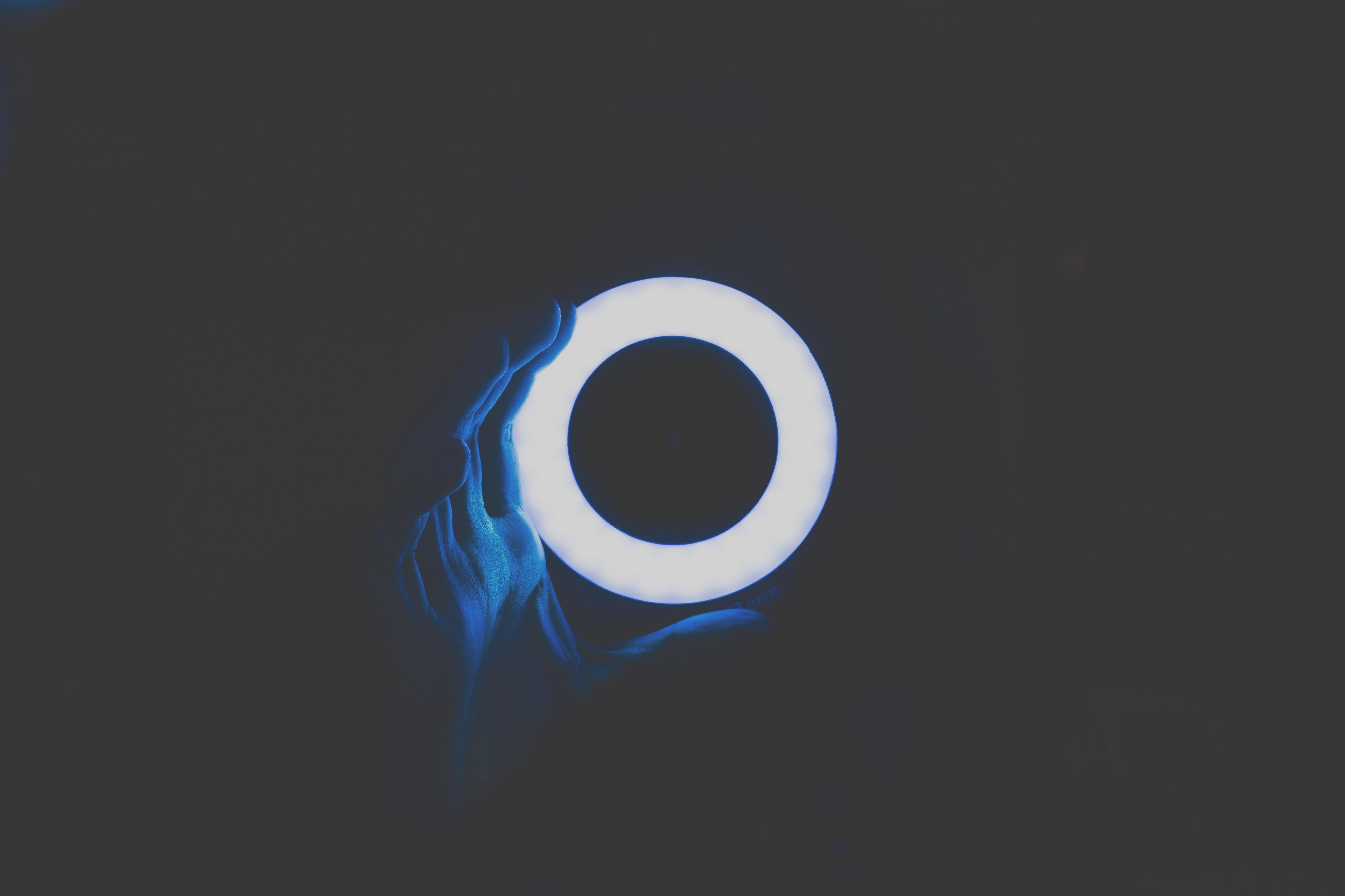 A ring lamp illuminates a hand in the dark.