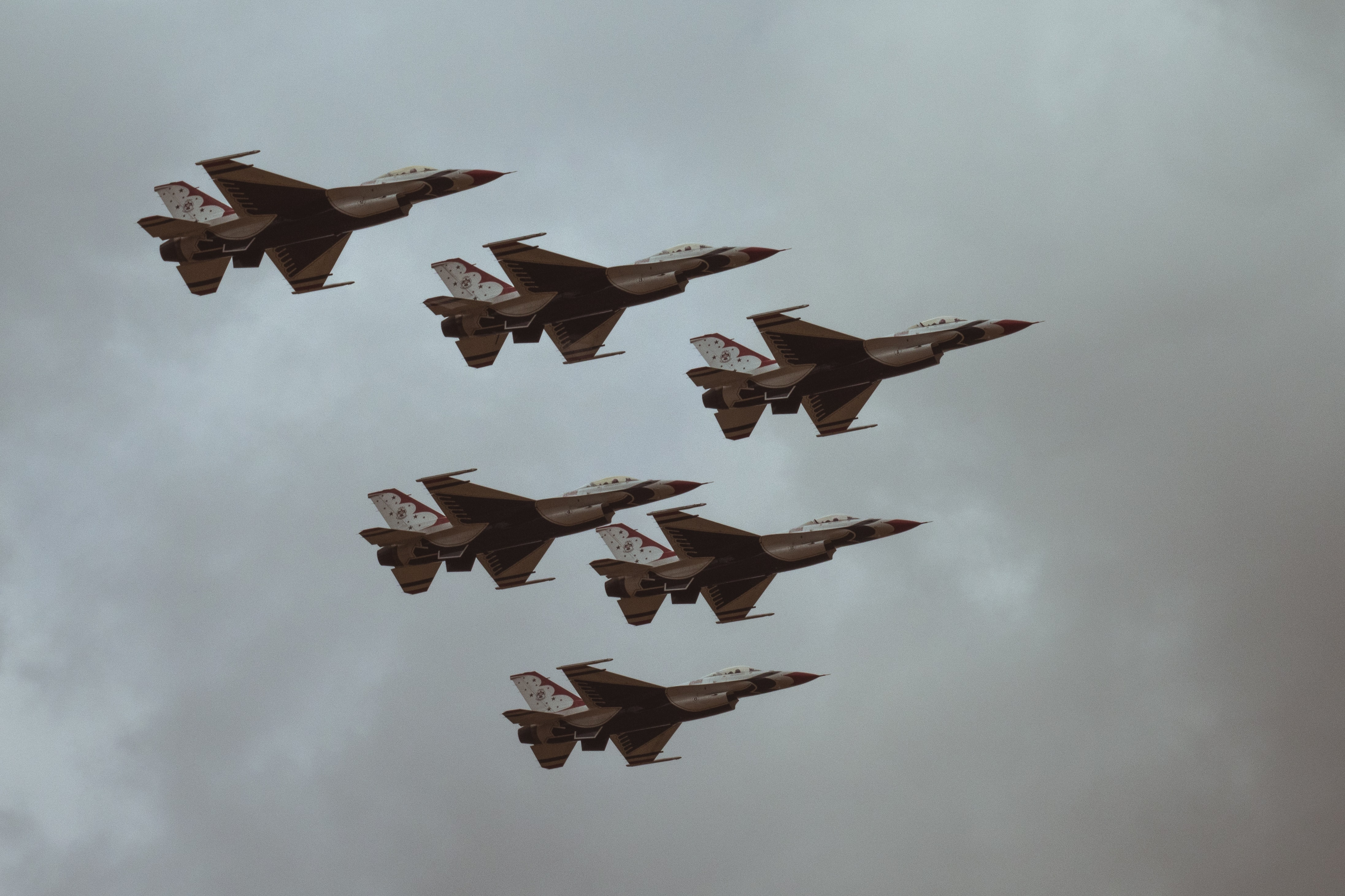 Six fighter jets flying in a formation against a cloudy sky