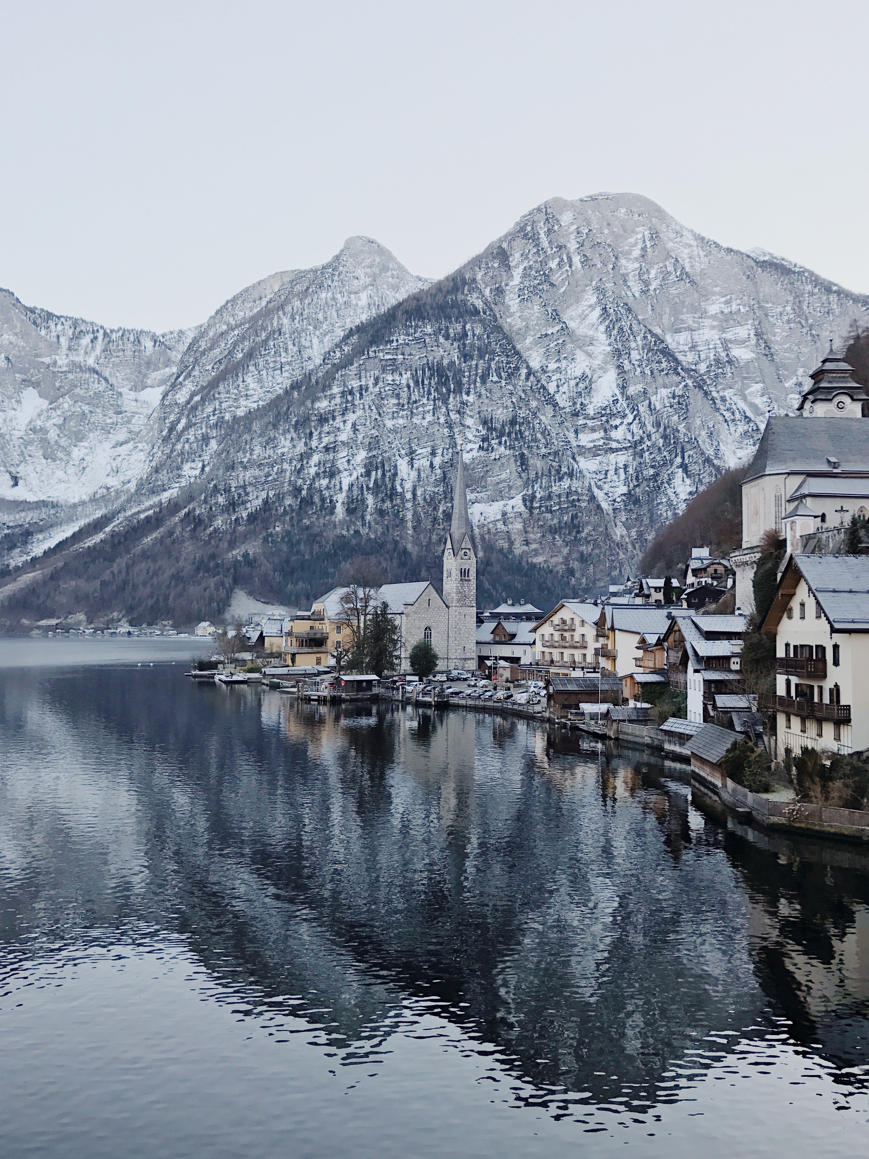 A church at a lake with snow capped mountains in the background