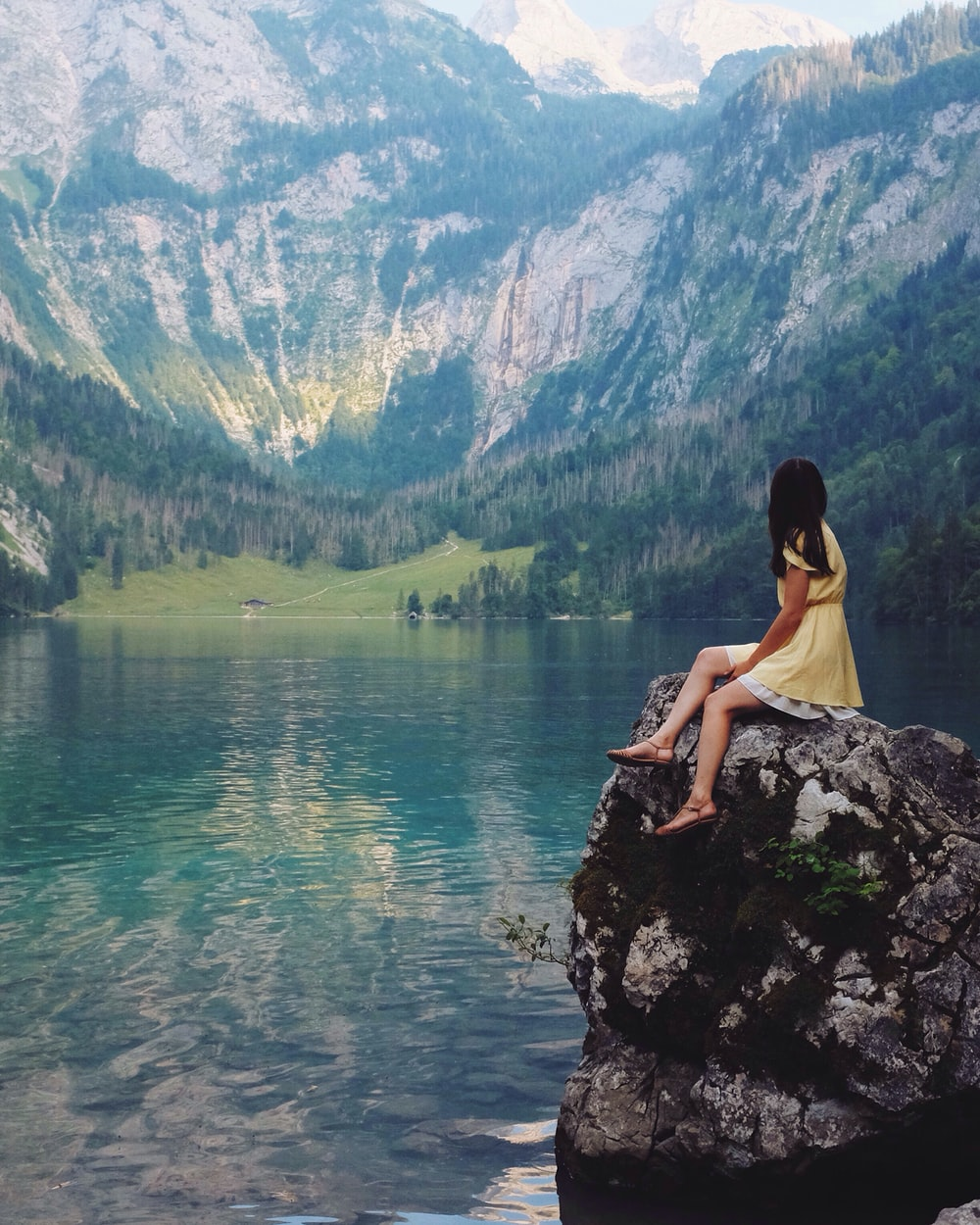 woman sitting on rock near lake