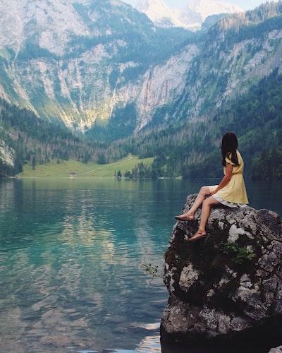 woman sitting on rock near lake
