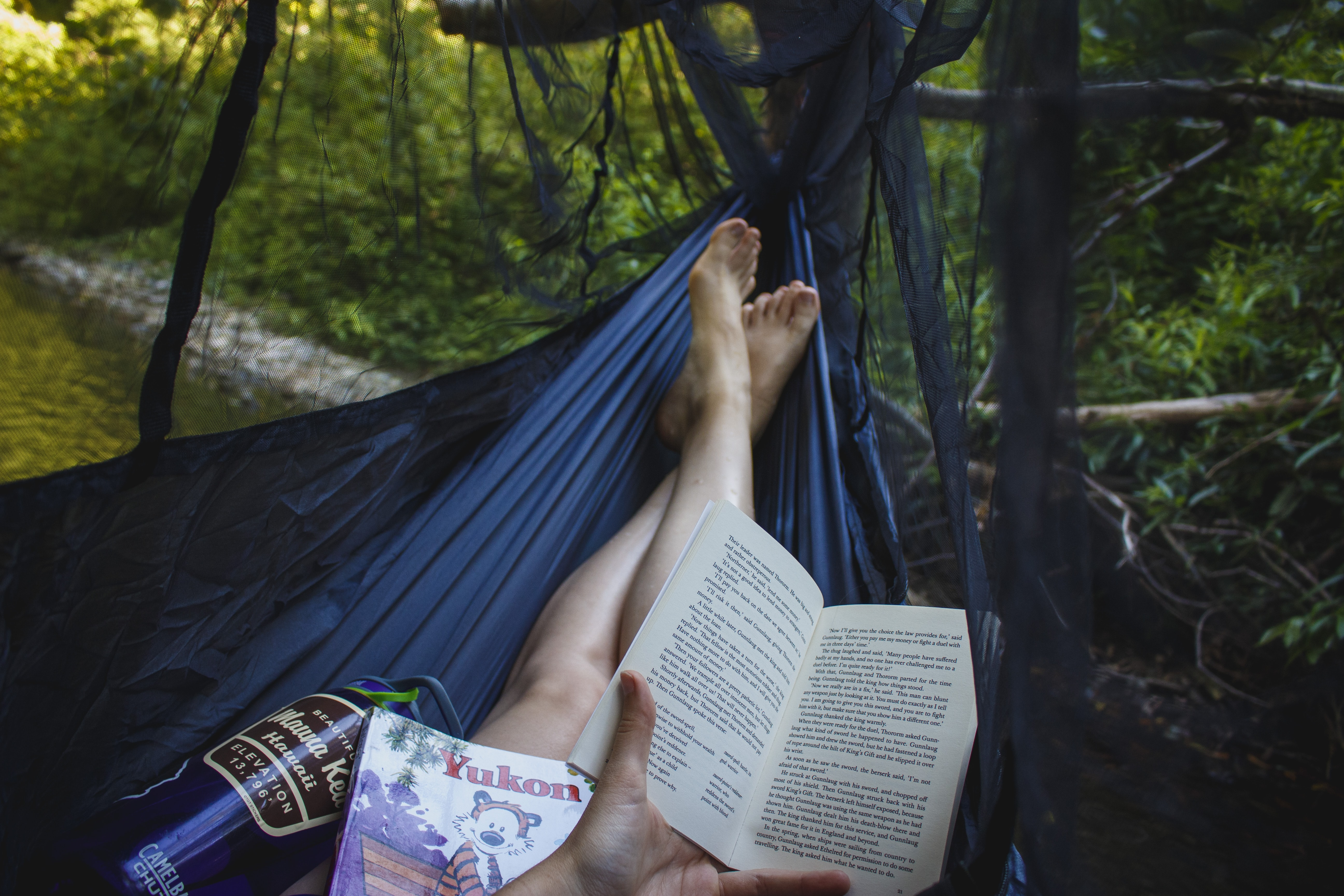 Person relaxing in a hammock reading books and drinking water