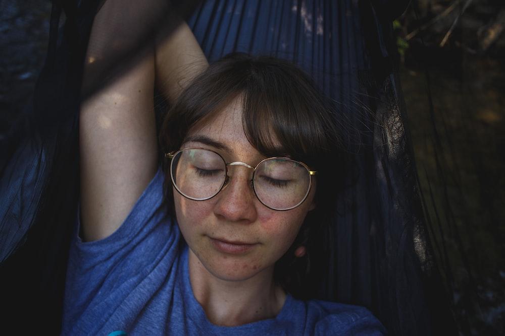 woman in blue crew-neck T-shirt laying on black hammock