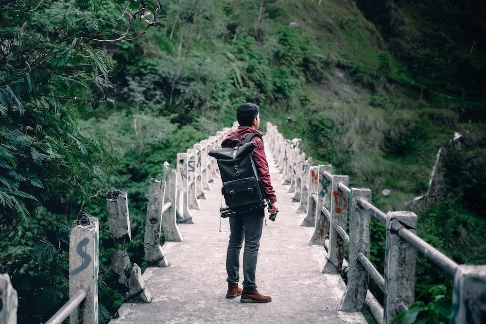 man standing on gray concrete bridge taken at daytime
