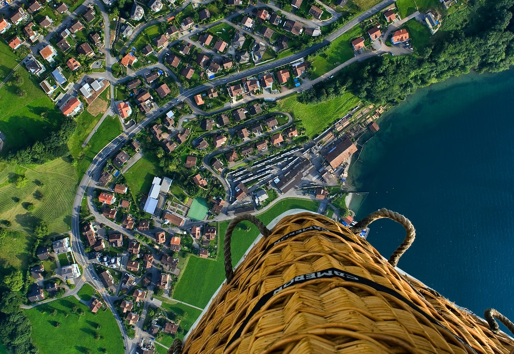 person riding hot air balloon taking photo of village near sea during daytime