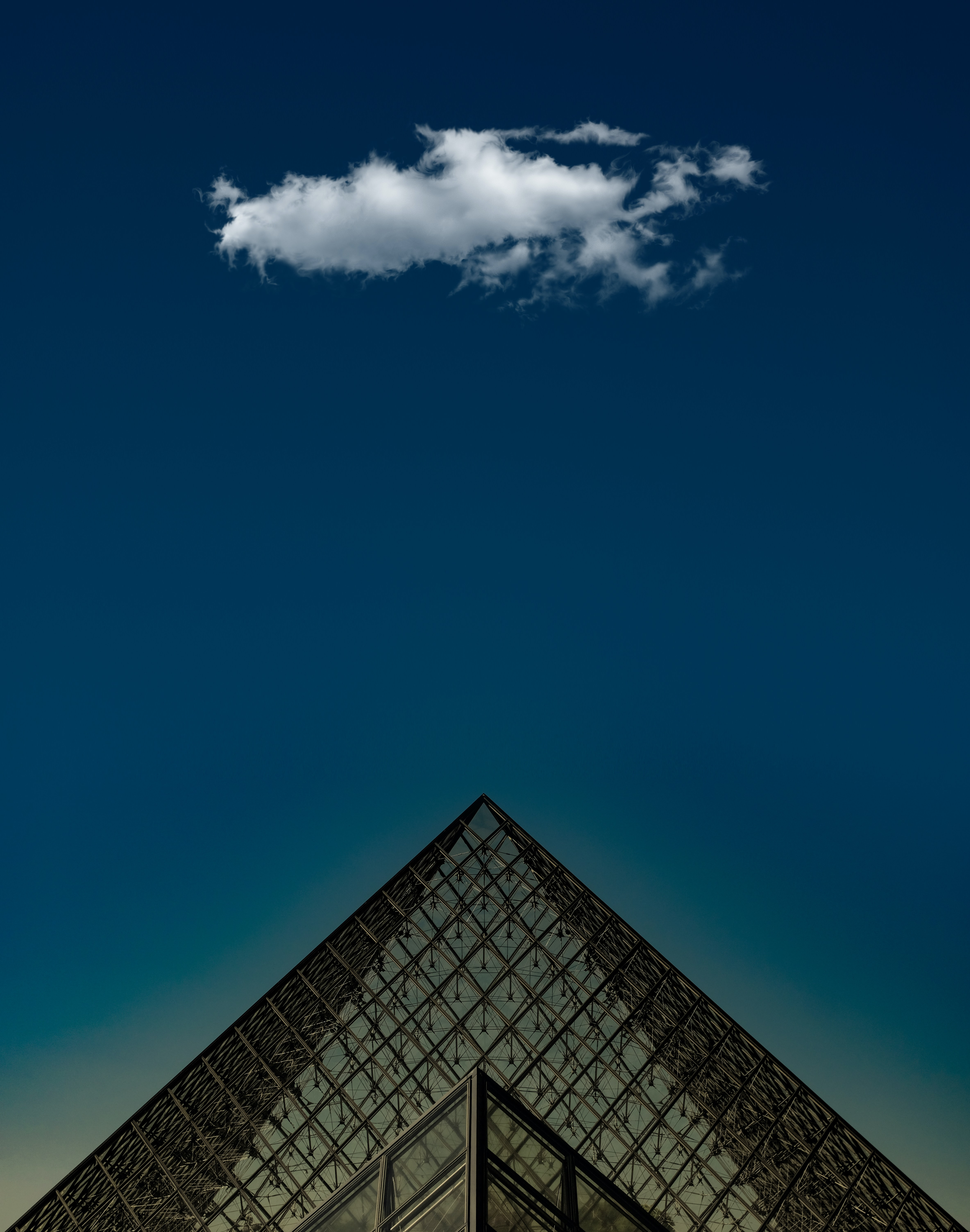 A small cloud in the deep blue sky above the triangular pyramid in front of the Louvre