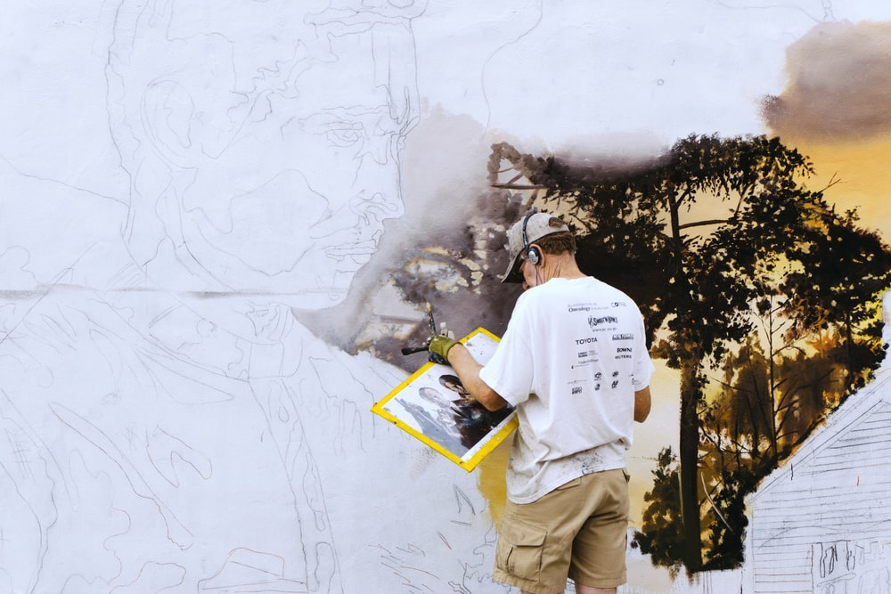 man wearing black headphones near white wall paint