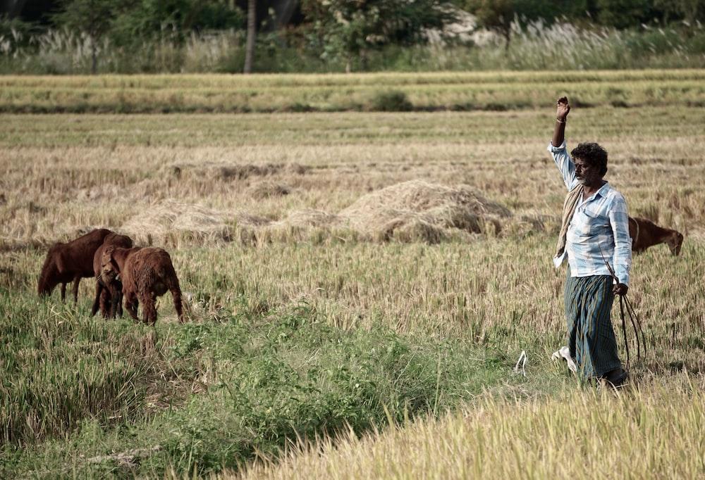 man raising right hand on grass field