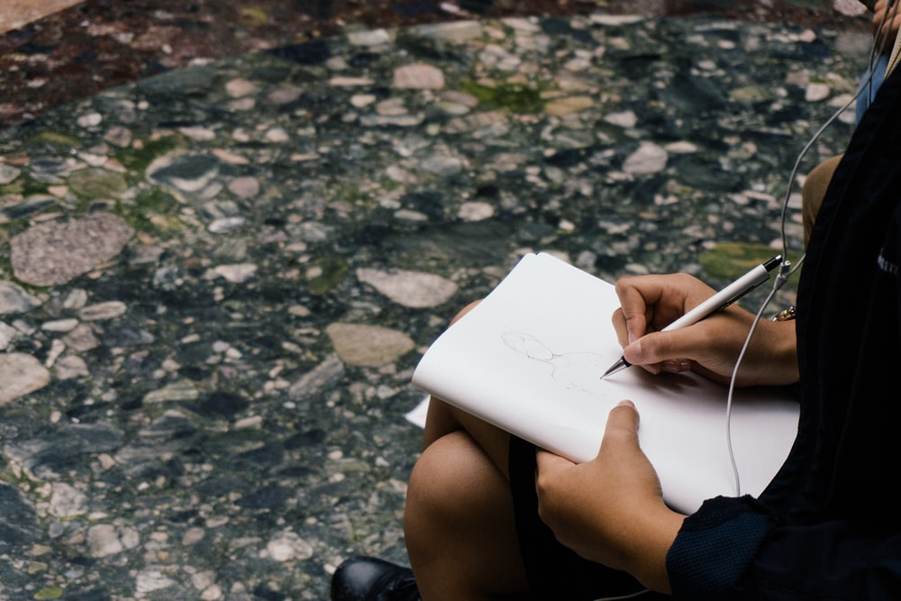 person sitting while writing