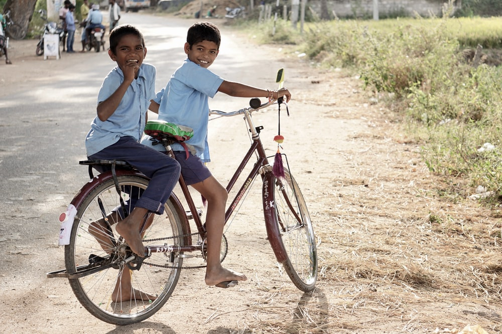 two boy riding on red step-through bicycle during daytime