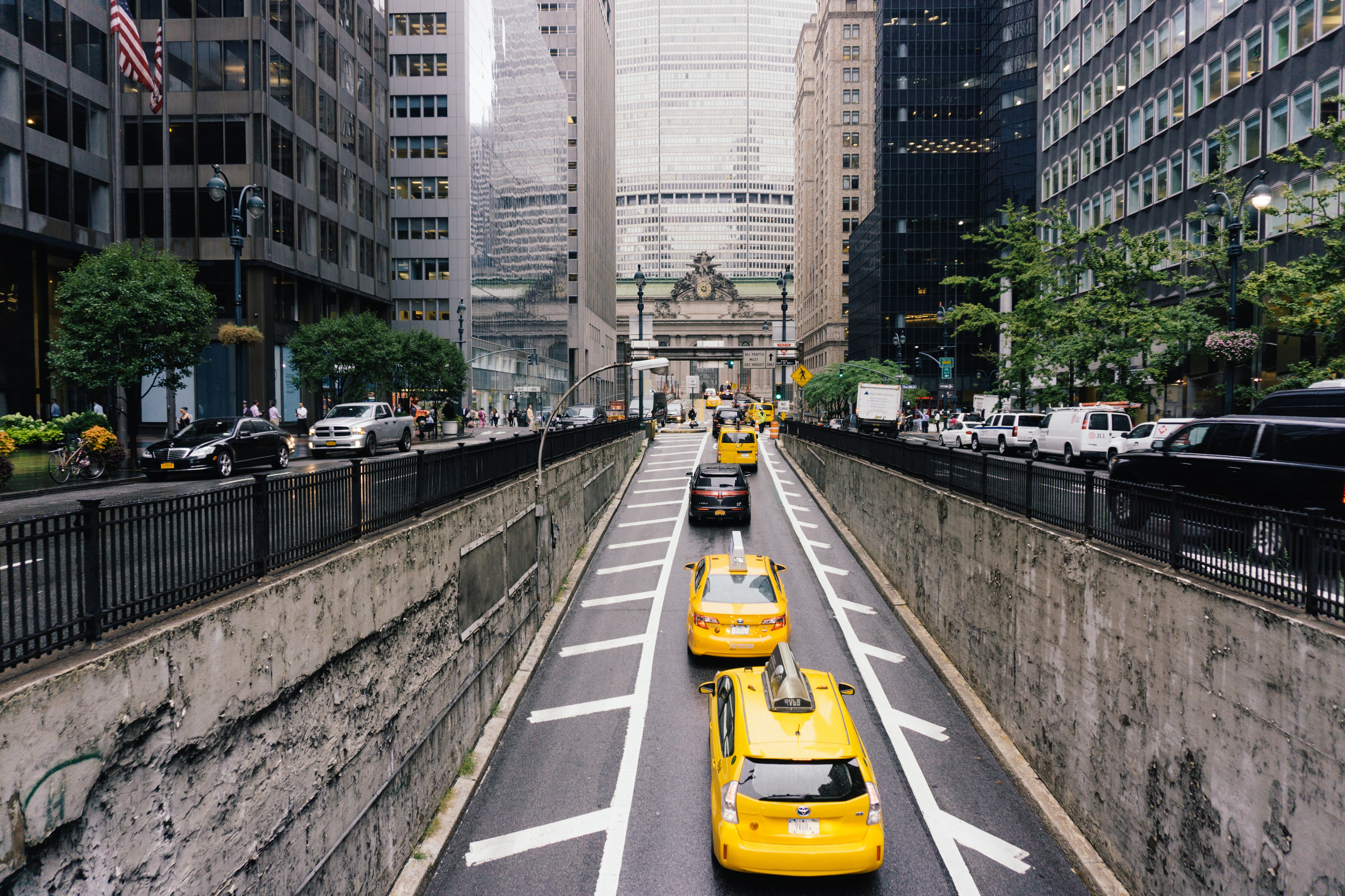 Line of yellow taxi cabs drive down a busy city street