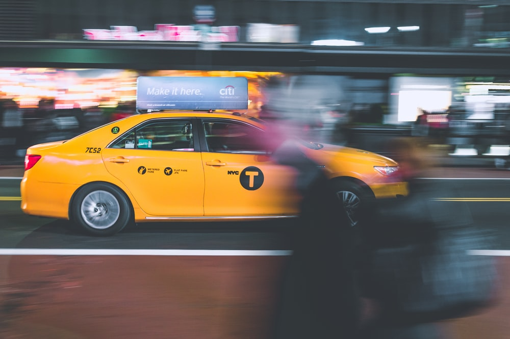 yellow sedan on gray road