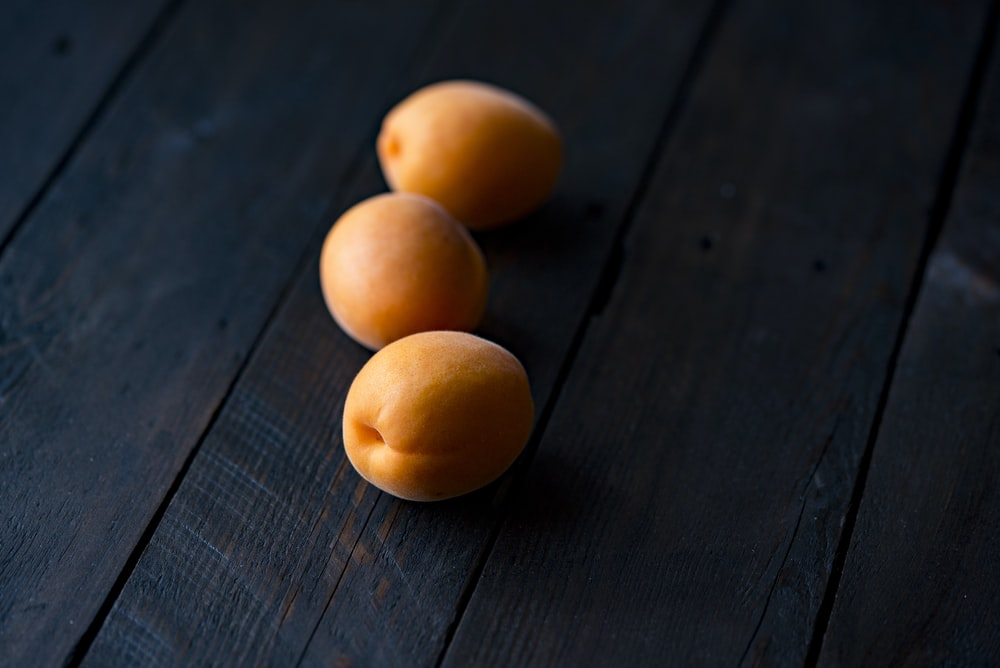 three fruits on wooden surface