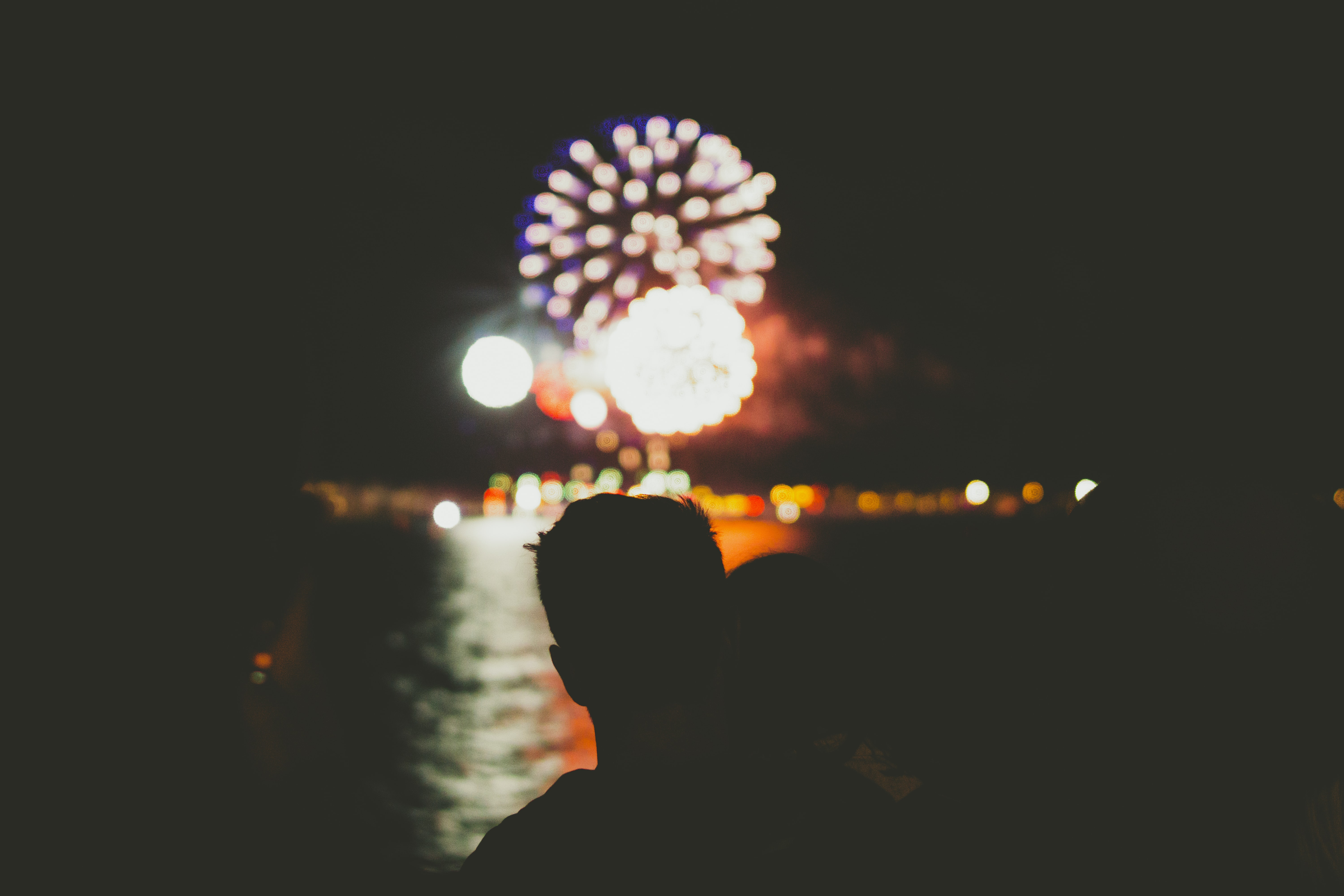 silhouette of person in front of fireworks