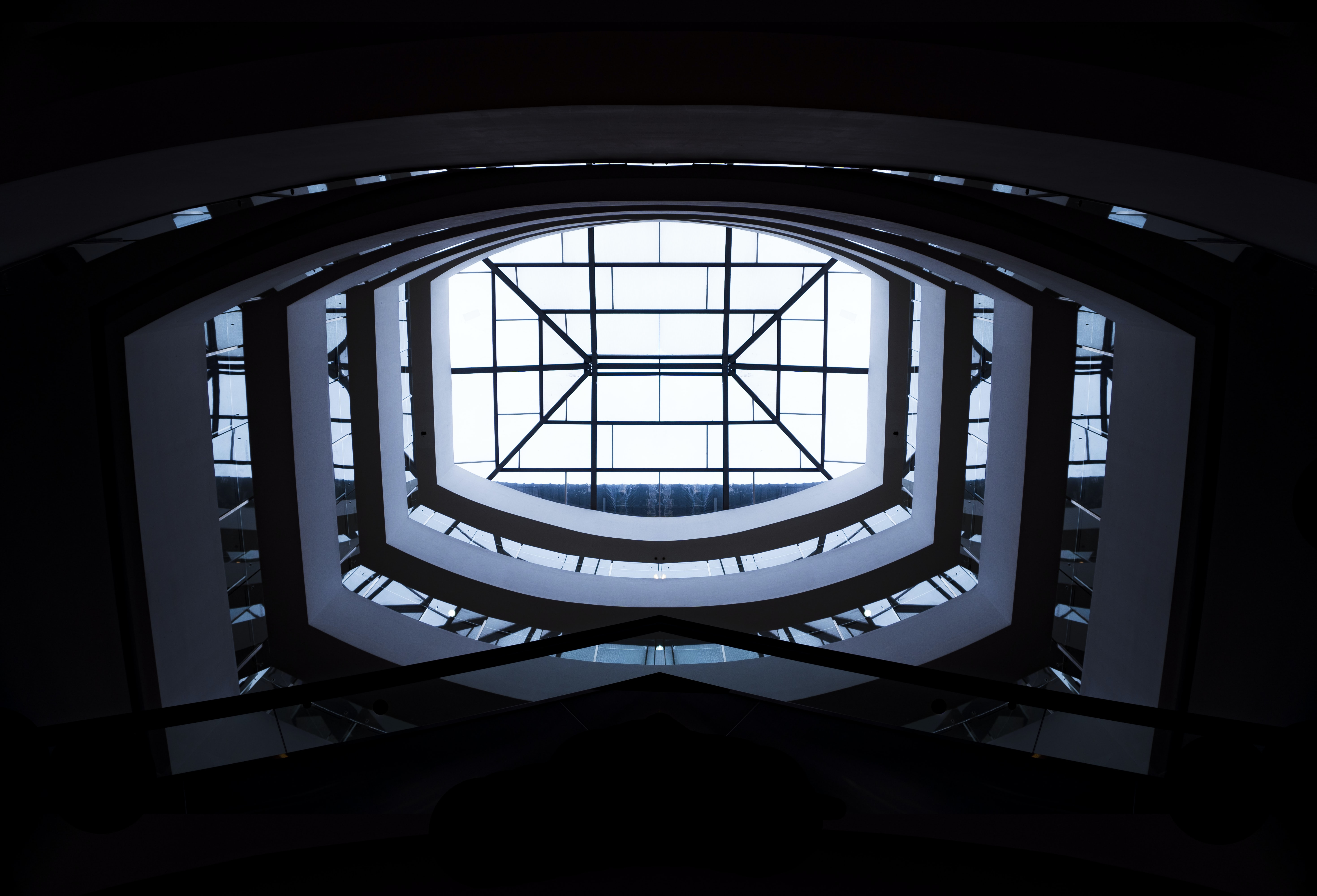 low-angle photography of white building interior with clear glass roof during daytime