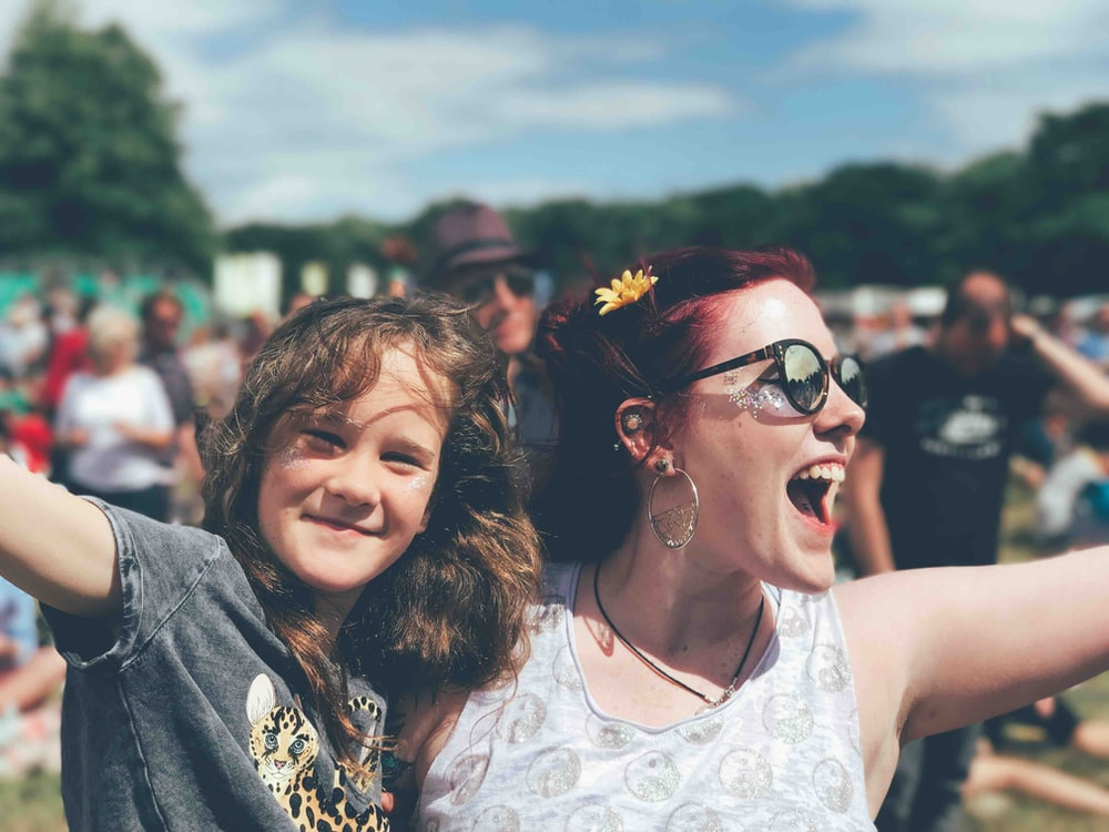 girl and woman near people at the field during day